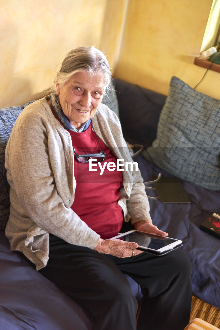 sitting, three quarter length, technology, senior adult, digital tablet, senior men, wireless technology, real people, sofa, communication, senior women, connection, holding, indoors, casual clothing, home interior, day, men, looking at camera, portability, lifestyles, portrait, senior couple, people