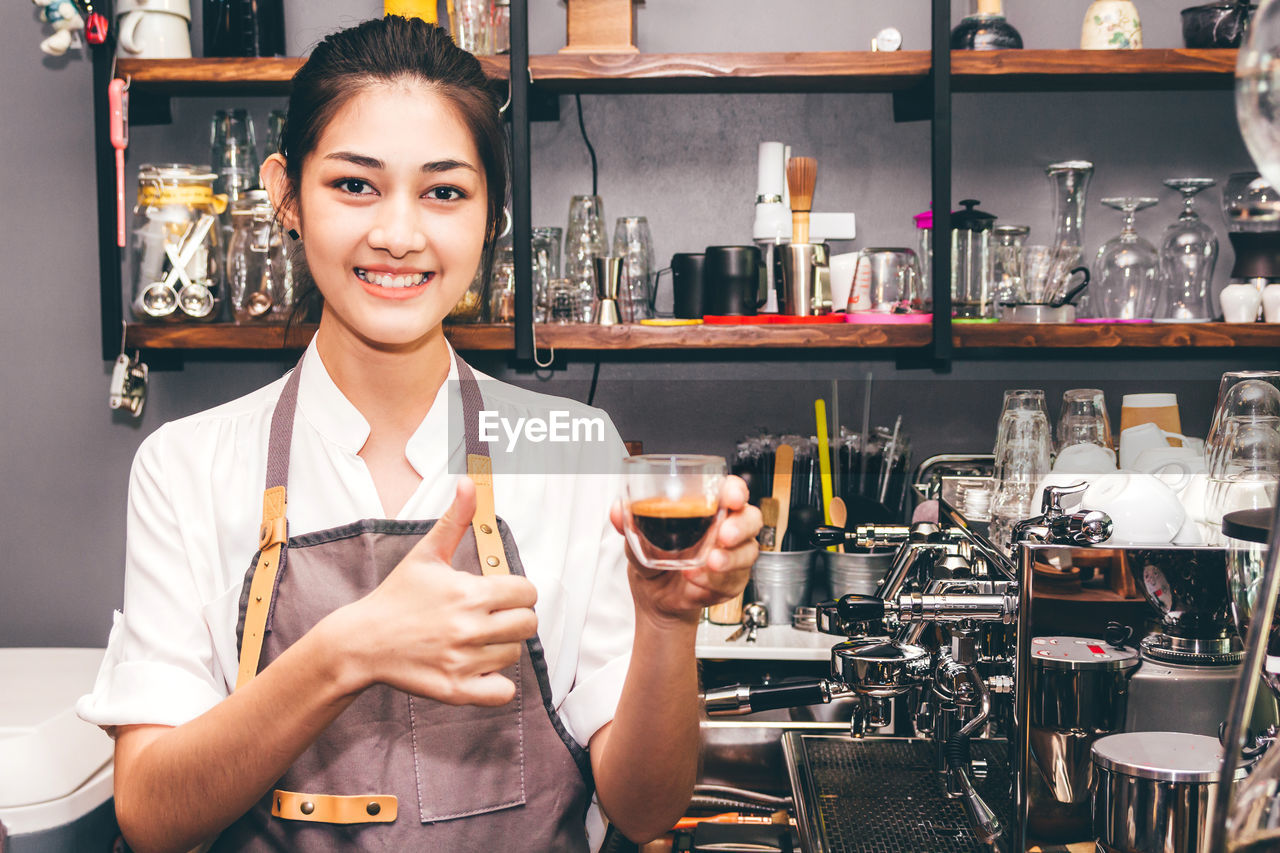 Portrait of smiling barista holding coffee at cafe
