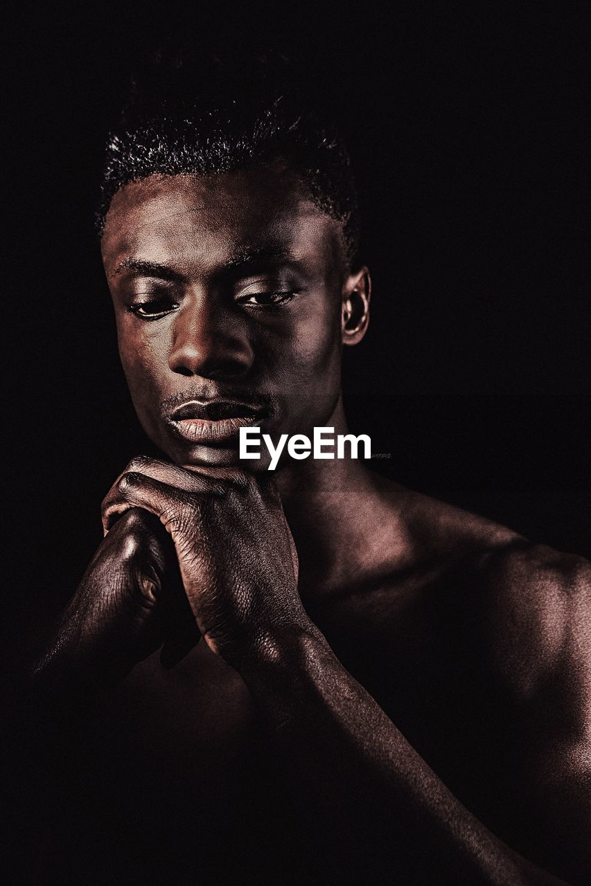 shirtless, studio shot, one person, black background, young adult, real people, young men, strength, portrait, lifestyles, looking at camera, muscular build, indoors, men, headshot, boxing glove, close-up, masculinity