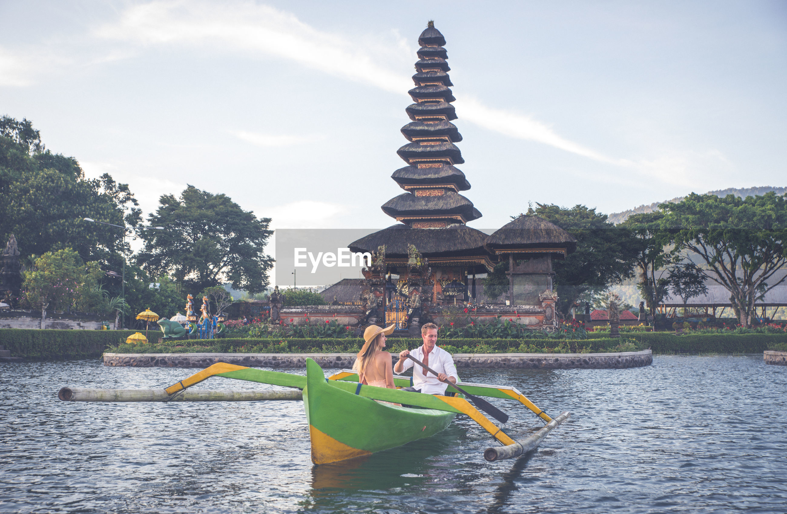 Couple in outrigger boat on lake against temple