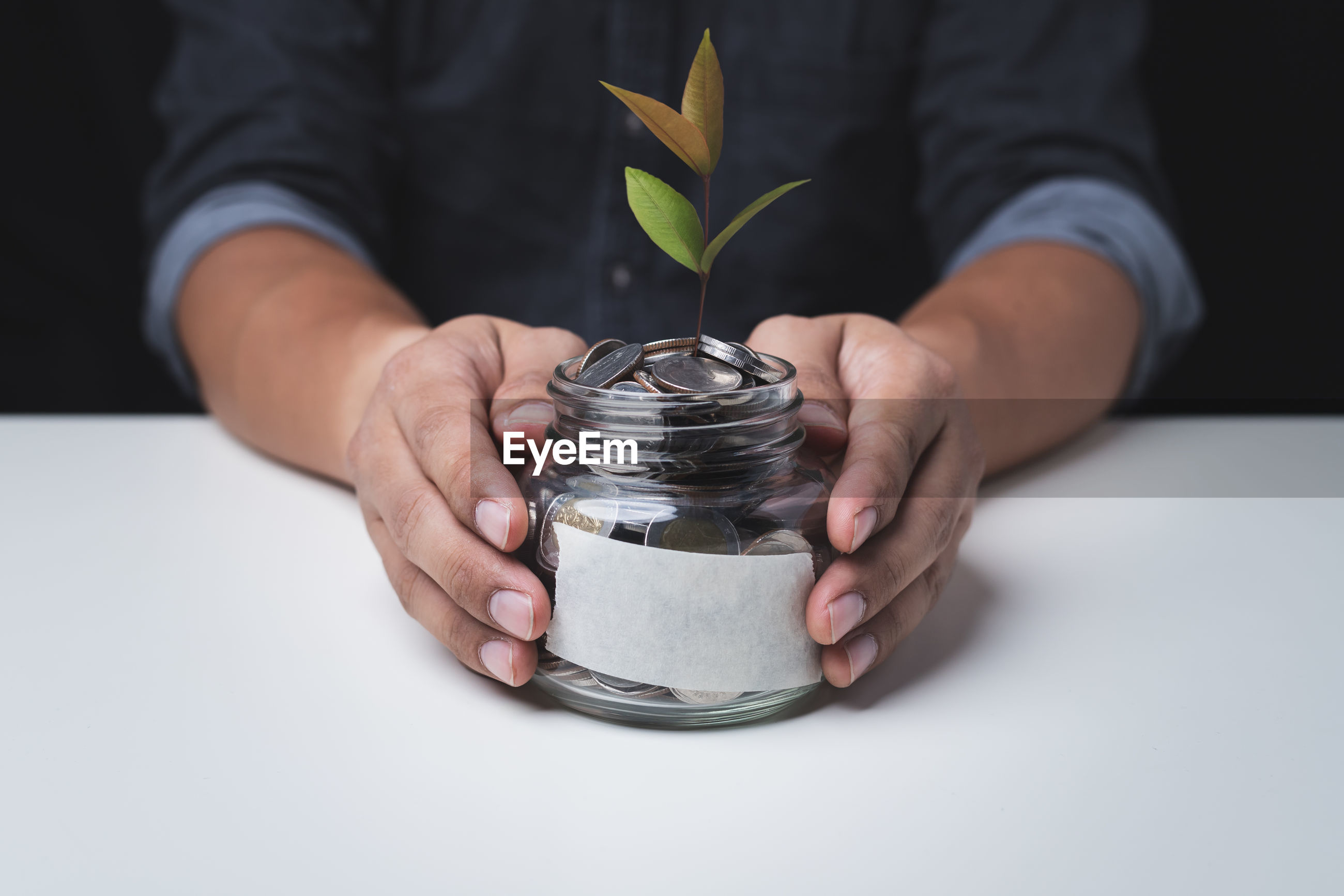 Close up hand of a man holding a glass jar with a coin inside concept of saving and investment