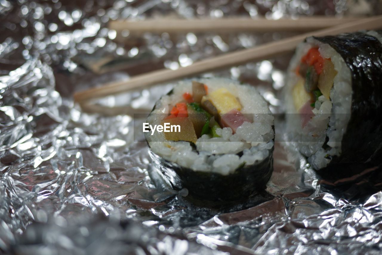 Close-Up Of Sushi And Chopsticks In Foil