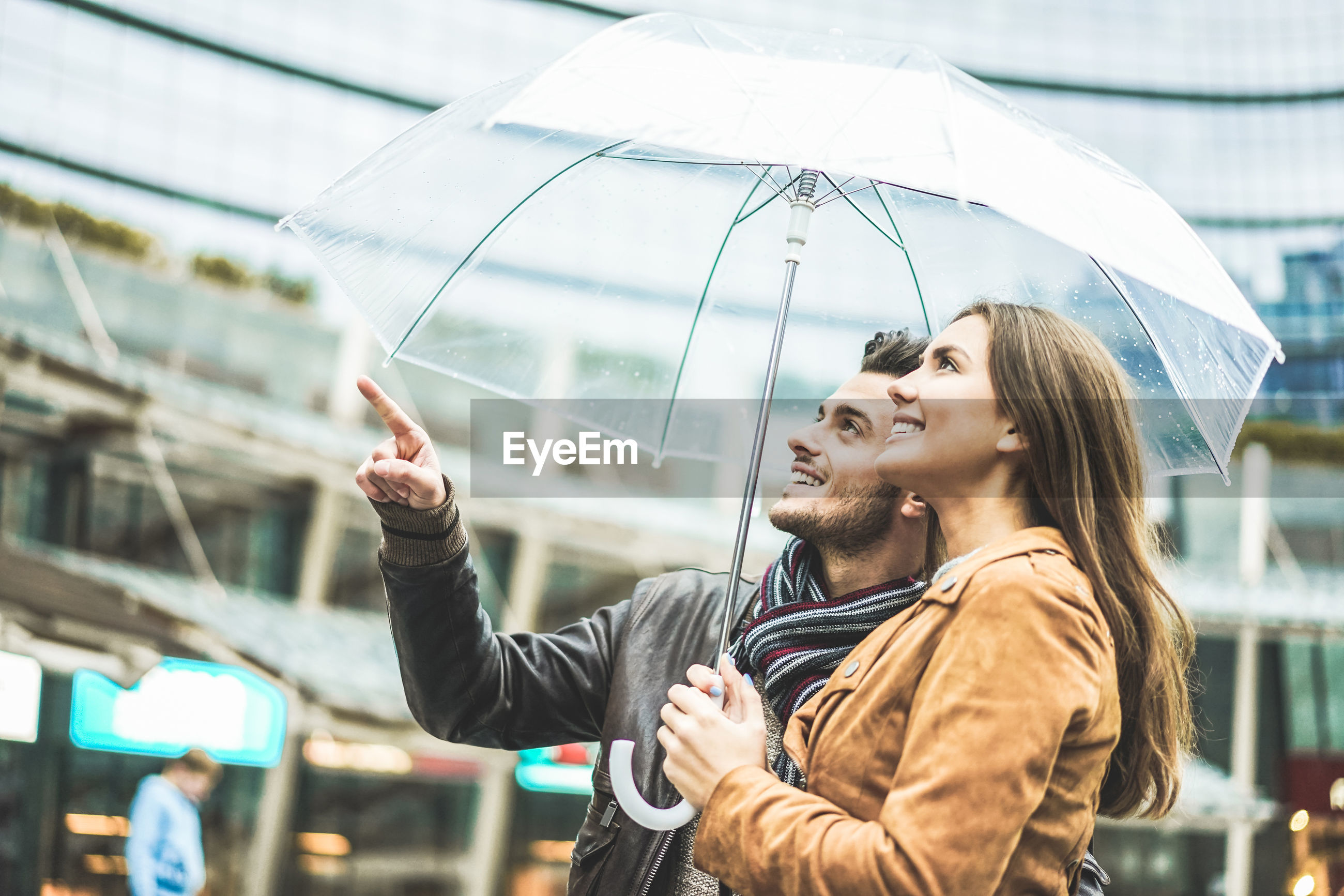 Man pointing while woman holding umbrella in city