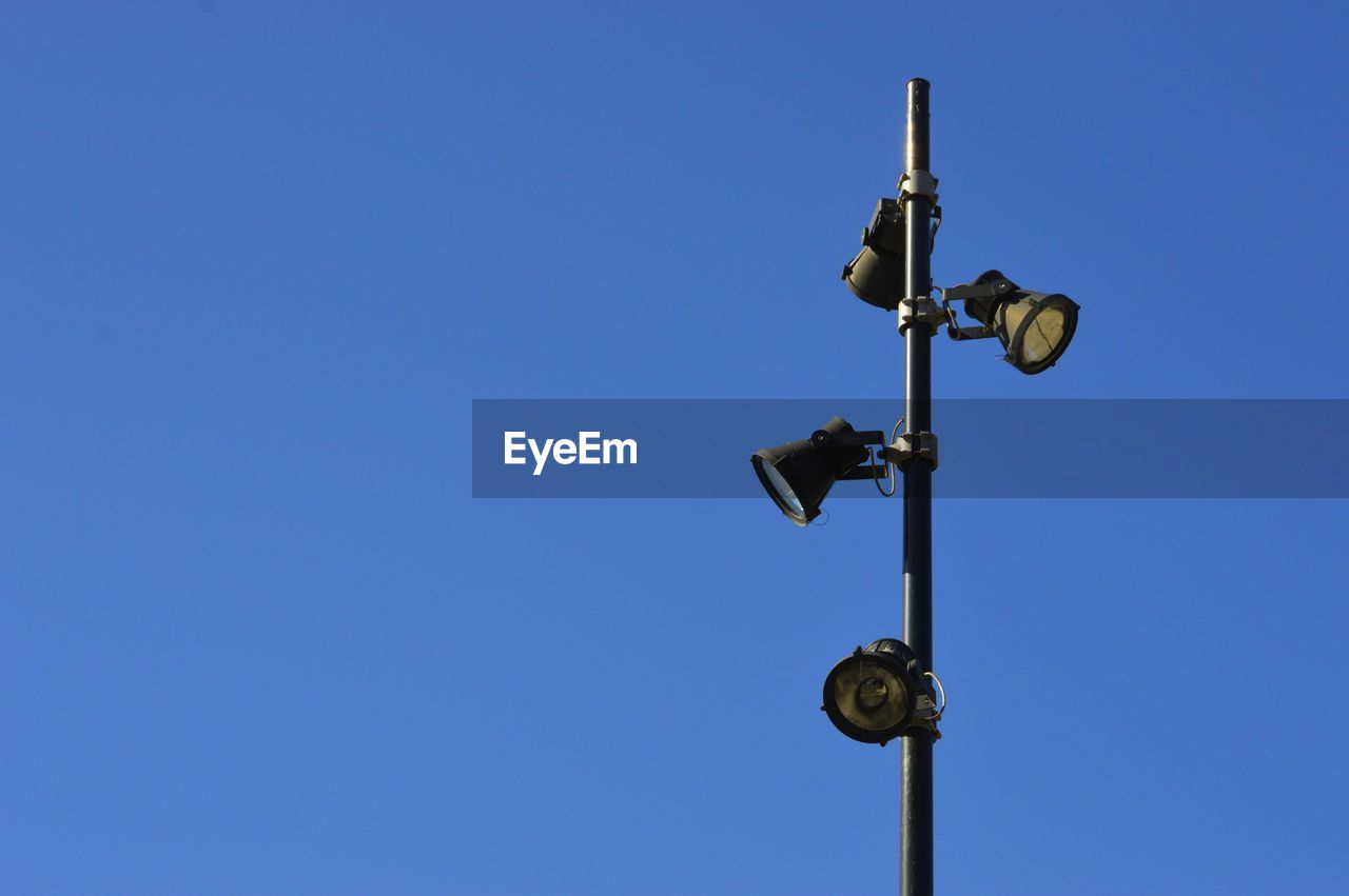 clear sky, copy space, blue, sky, low angle view, no people, nature, technology, day, outdoors, lighting equipment, metal, guidance, electricity, sunlight, connection, close-up, pole, safety, security system, power supply