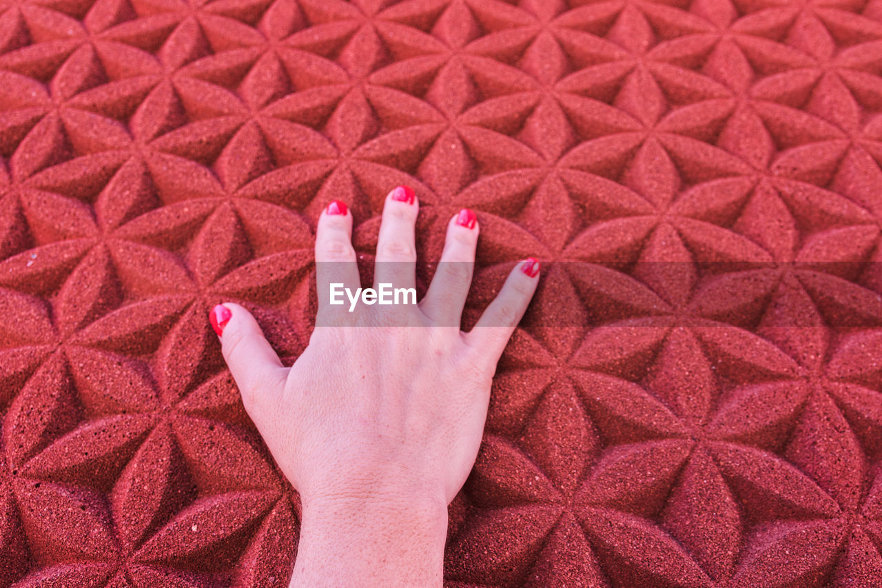 Cropped hand of woman touching patterned red wall