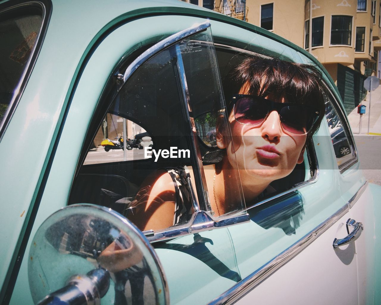 Portrait of young woman puckering lips while peeking from car window