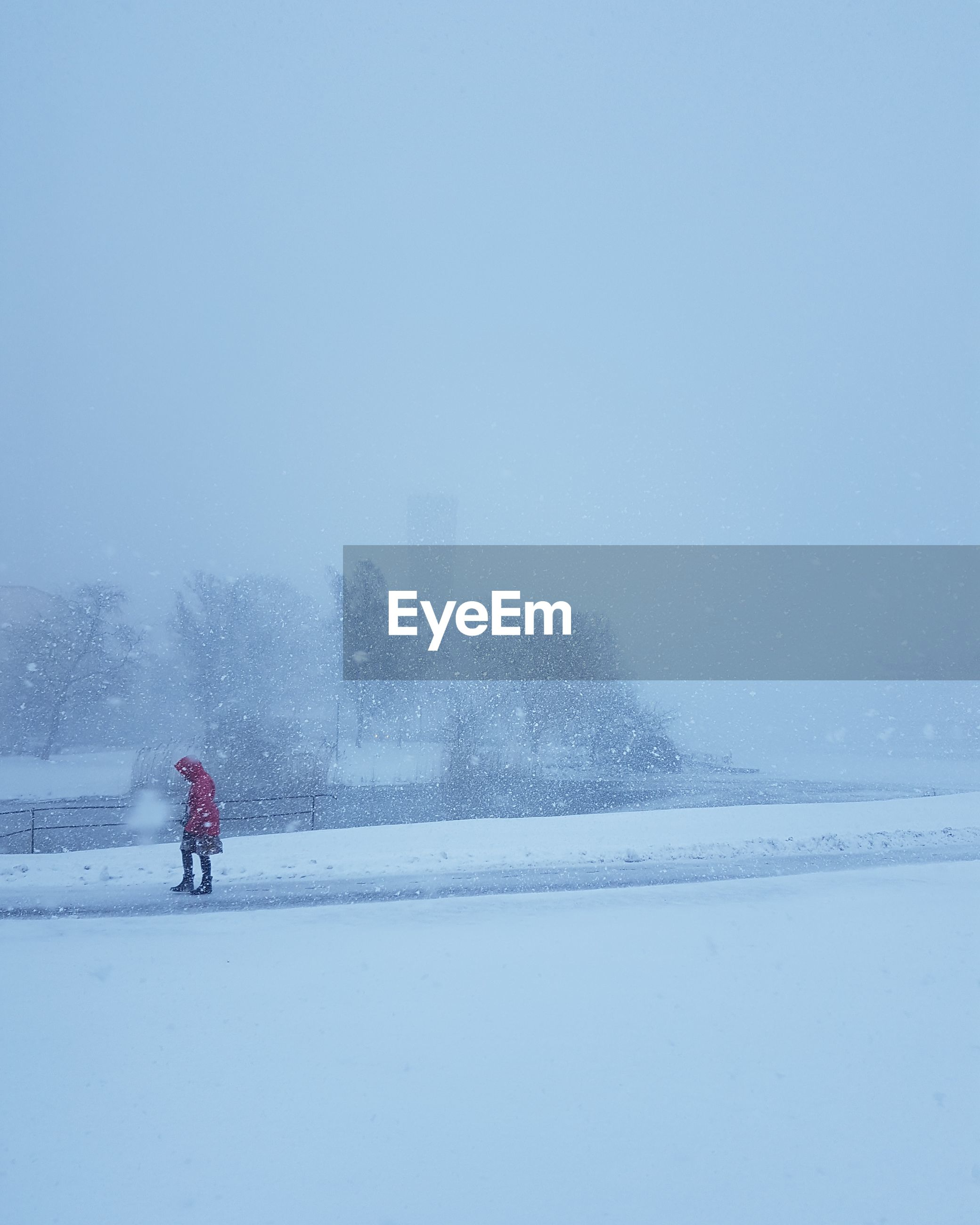 Woman walking on road against clear sky during snowfall