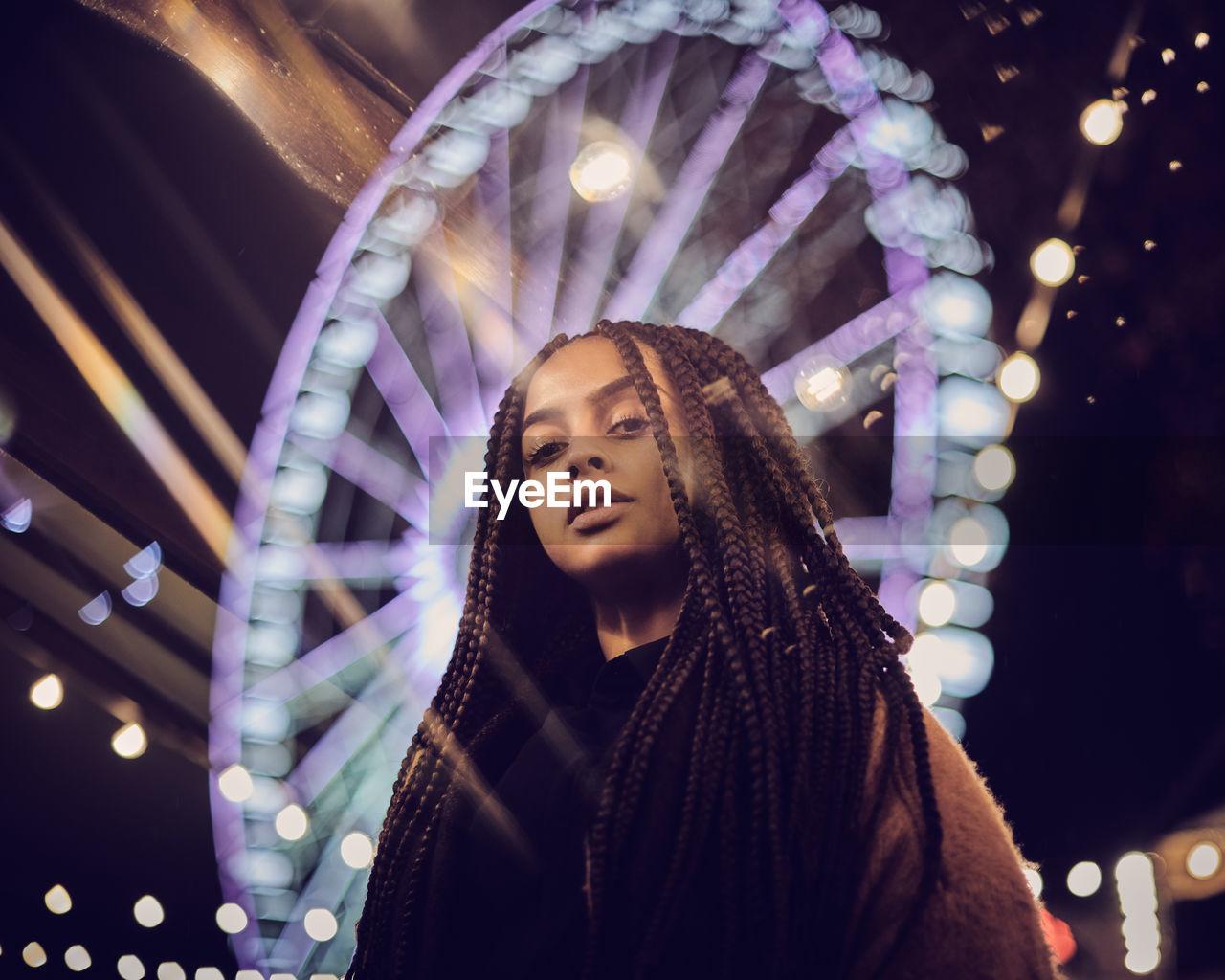 Portrait Of Woman Standing Against Illuminated Ferris Wheel At Night
