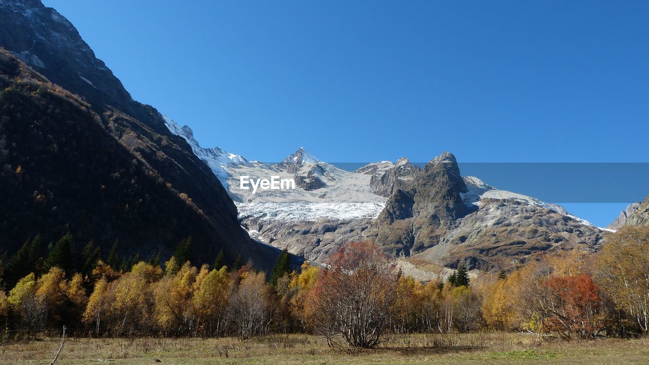 mountain, beauty in nature, scenics - nature, tranquility, plant, tranquil scene, nature, clear sky, mountain range, environment, sky, tree, landscape, non-urban scene, cold temperature, no people, winter, day, snow, mountain peak, outdoors, snowcapped mountain, formation