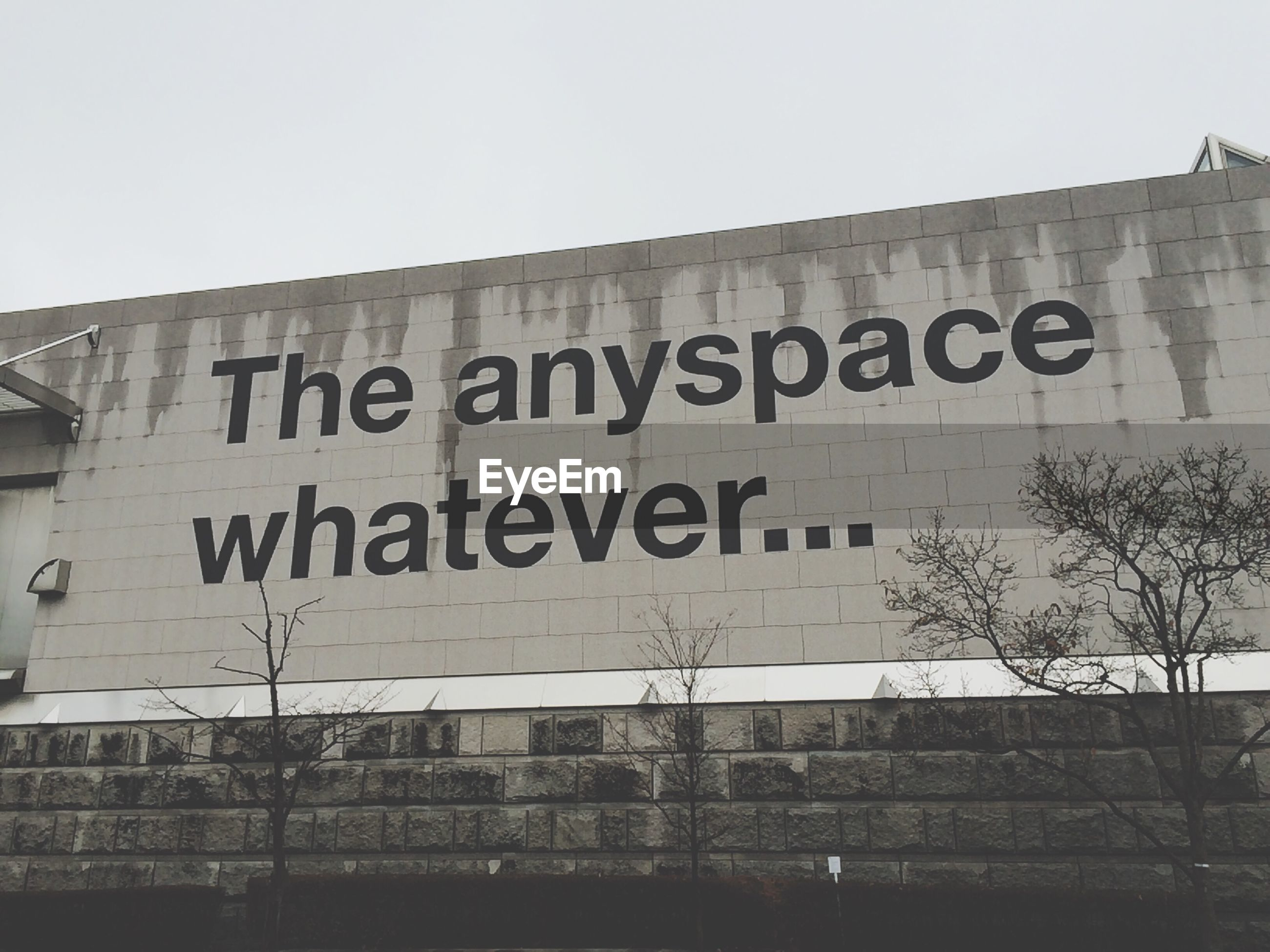 architecture, built structure, building exterior, text, western script, clear sky, low angle view, communication, graffiti, building, city, non-western script, capital letter, wall - building feature, day, outdoors, information, information sign, sky, sign