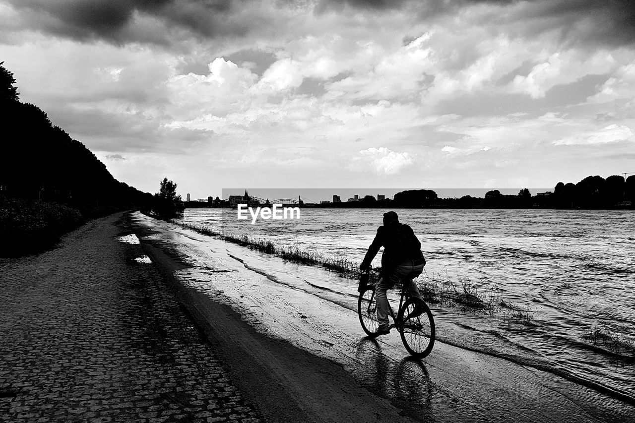 bicycle, transportation, real people, sky, one person, land vehicle, cloud - sky, lifestyles, riding, mode of transportation, ride, water, activity, cycling, men, road, nature, sport, outdoors