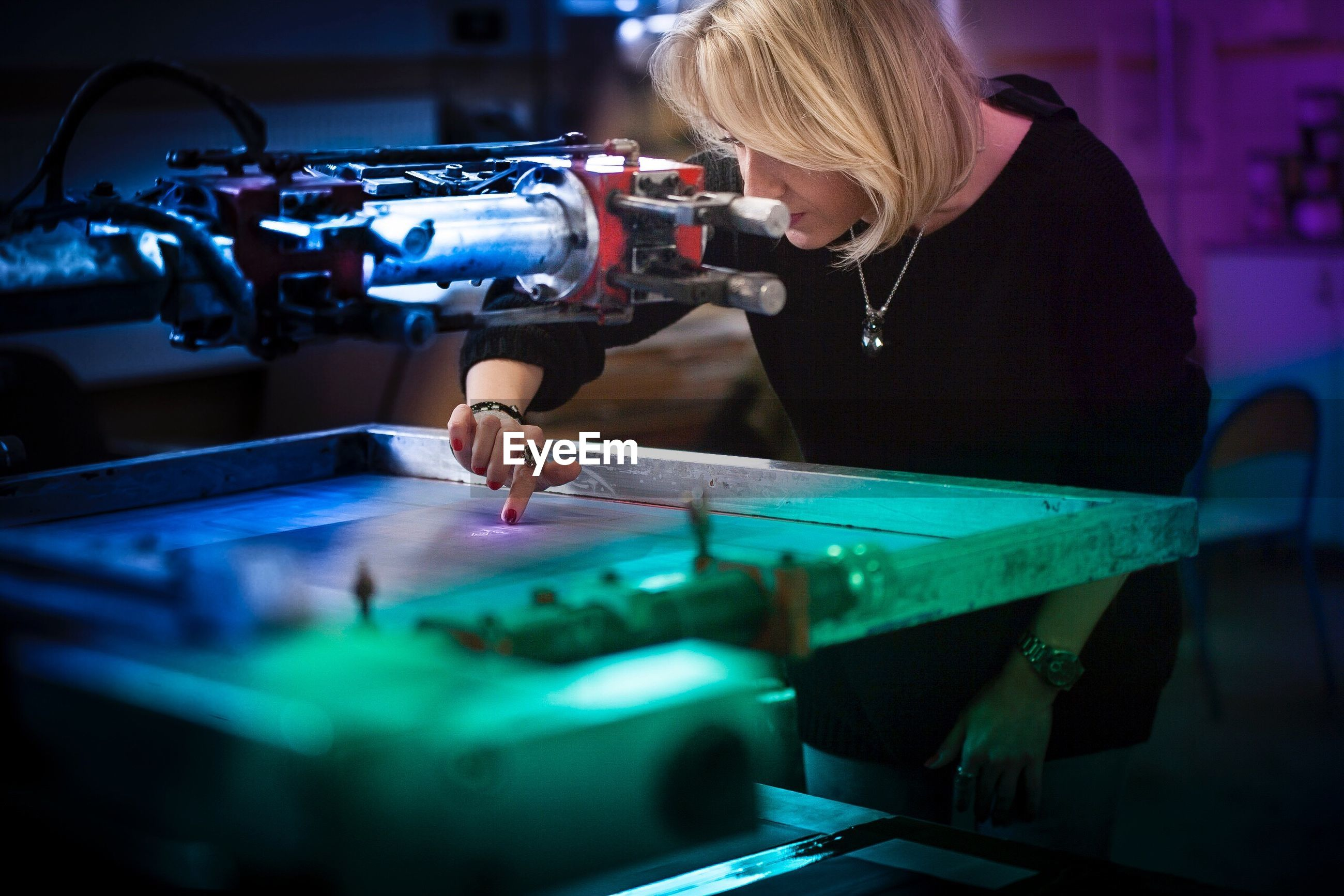 Businesswoman operating machinery at factory