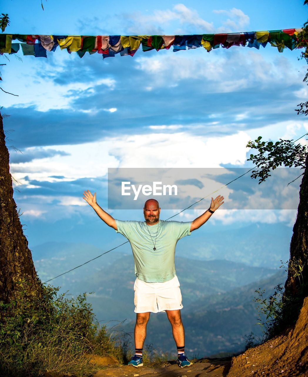 Man with arms outstretched standing on himalayas against cloudy sky