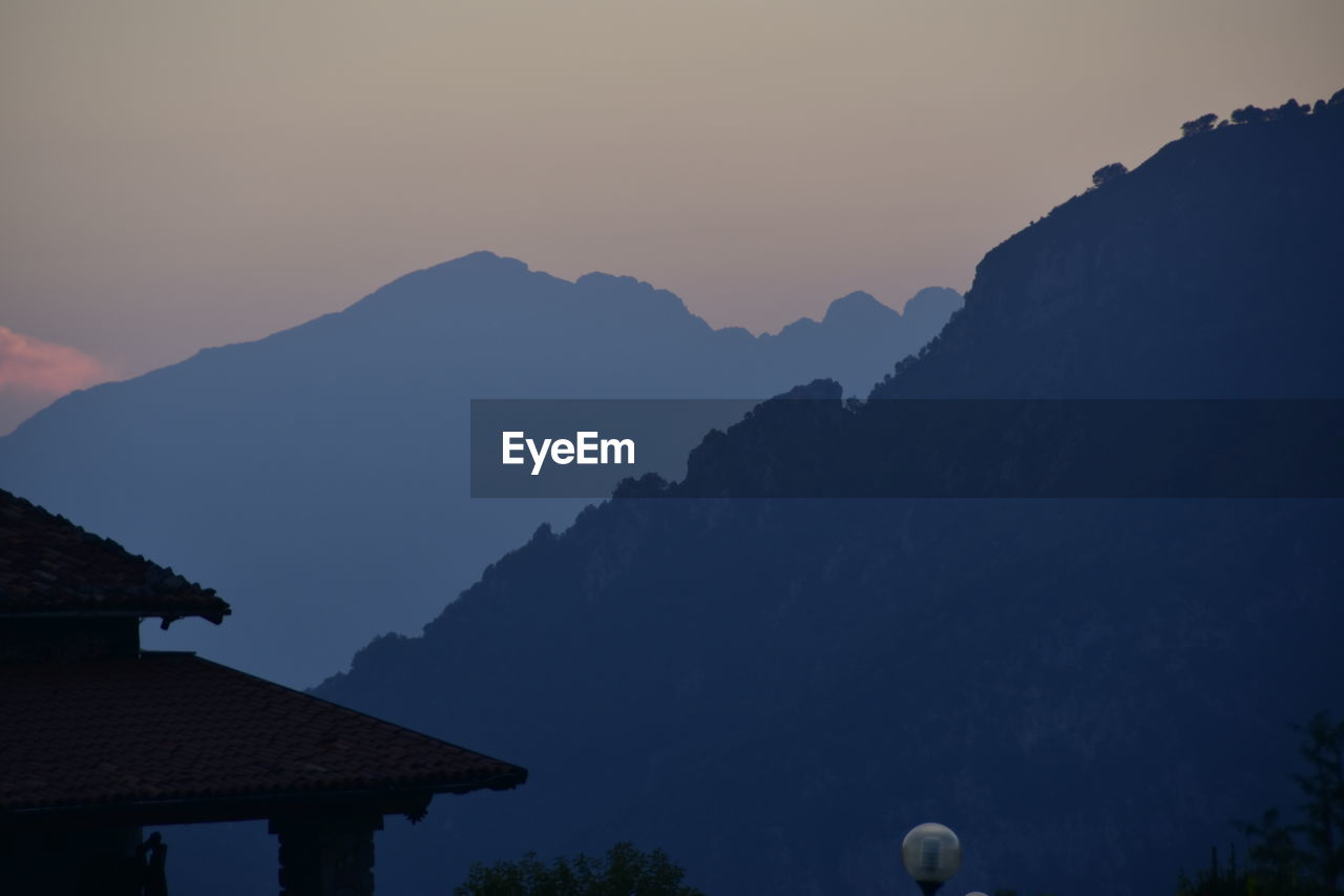 mountain, sky, mountain range, building exterior, architecture, no people, built structure, beauty in nature, scenics - nature, nature, building, roof, house, tranquility, outdoors, tranquil scene, sunset, silhouette, residential district, clear sky, mountain peak