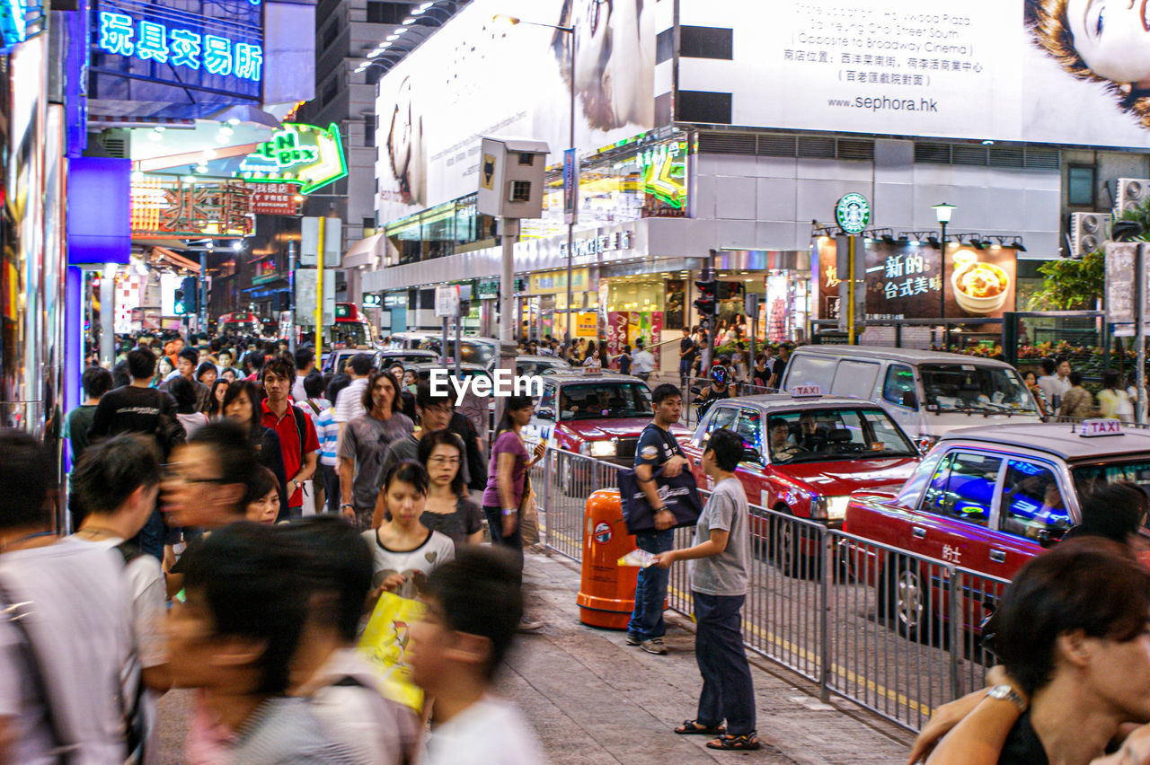 city, architecture, group of people, crowd, large group of people, motion, city life, street, building exterior, transportation, built structure, mode of transportation, women, men, adult, lifestyles, blurred motion, city street, real people, outdoors, busy