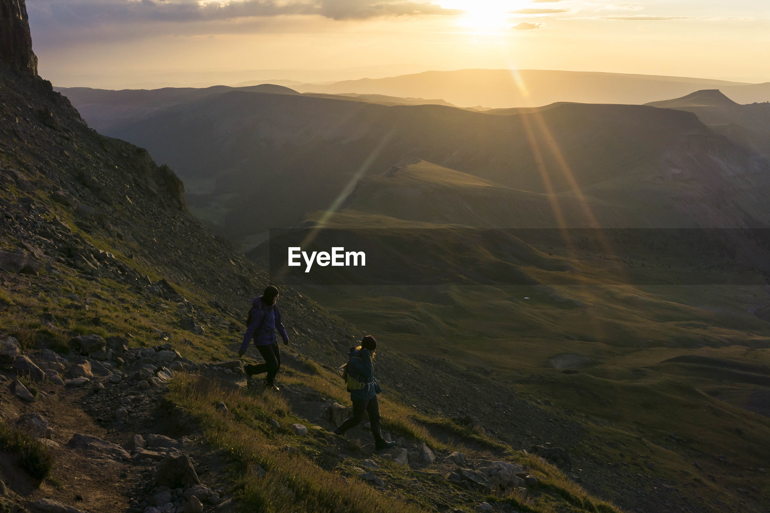 PEOPLE ON MOUNTAIN AGAINST SKY DURING SUNRISE
