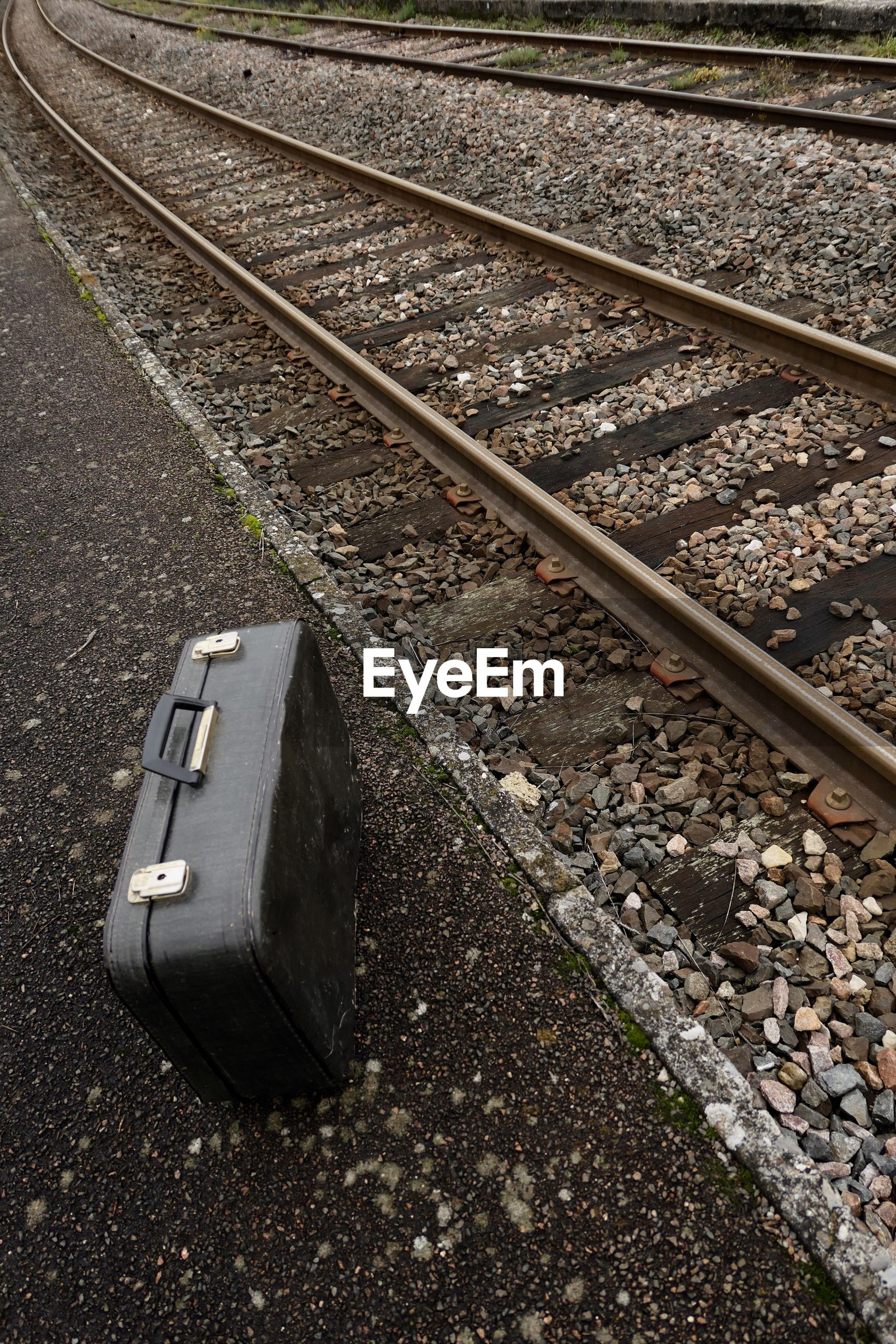 High Angle View Of Suitcase On Field By Railroad Track