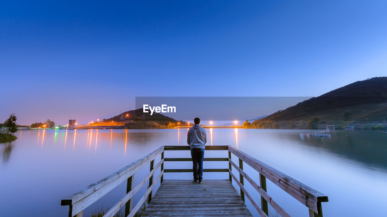 Rear View Of Man Standing On Pier At Dusk