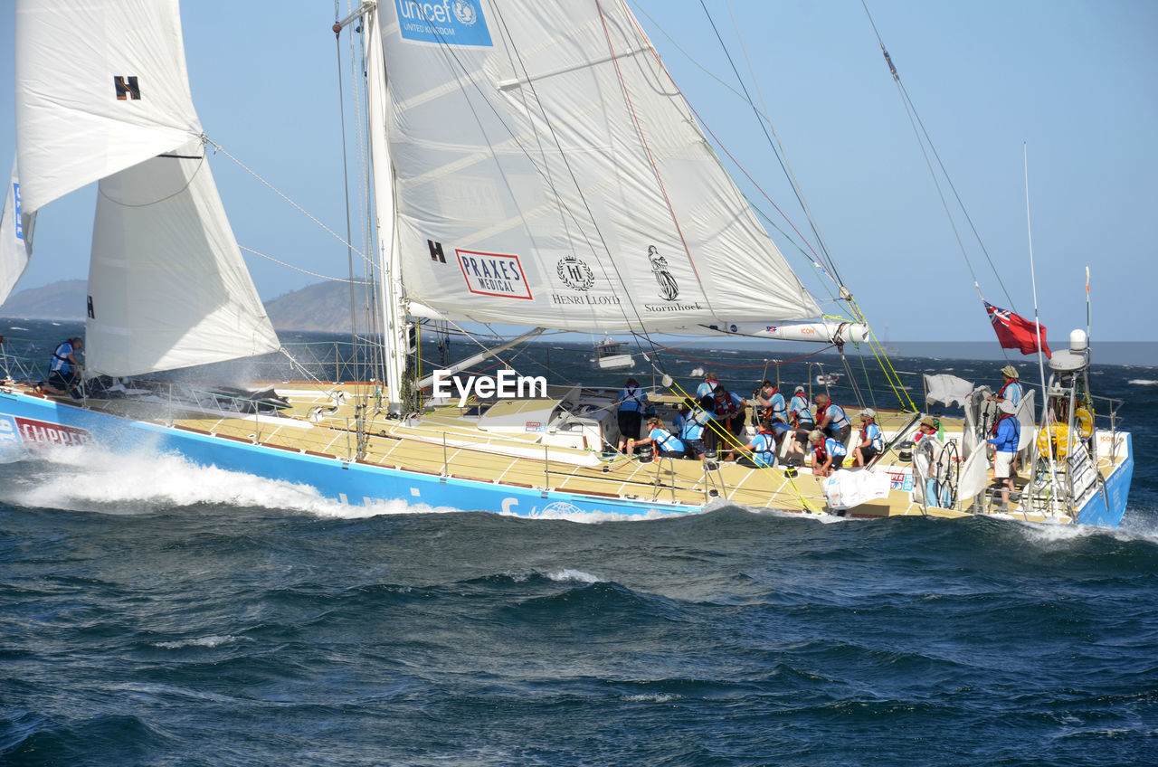 sea, nautical vessel, sailing, waterfront, transportation, water, day, sailboat, leisure activity, nature, adventure, outdoors, men, real people, sky, large group of people, sport, competition, wave, mast, extreme sports, sports race, people