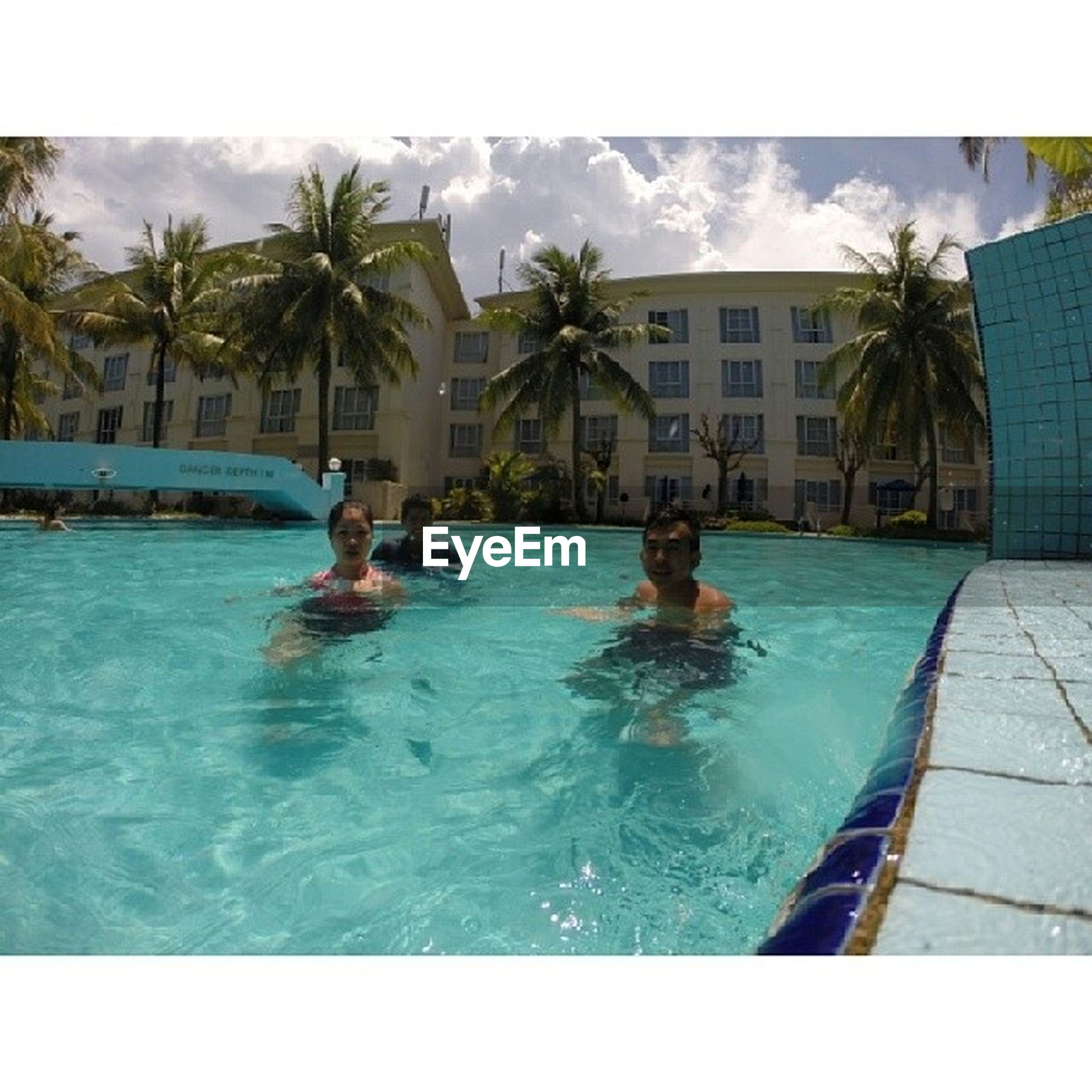 water, swimming pool, building exterior, transfer print, palm tree, lifestyles, architecture, built structure, leisure activity, waterfront, men, auto post production filter, tree, sea, swimming, day, sky, vacations