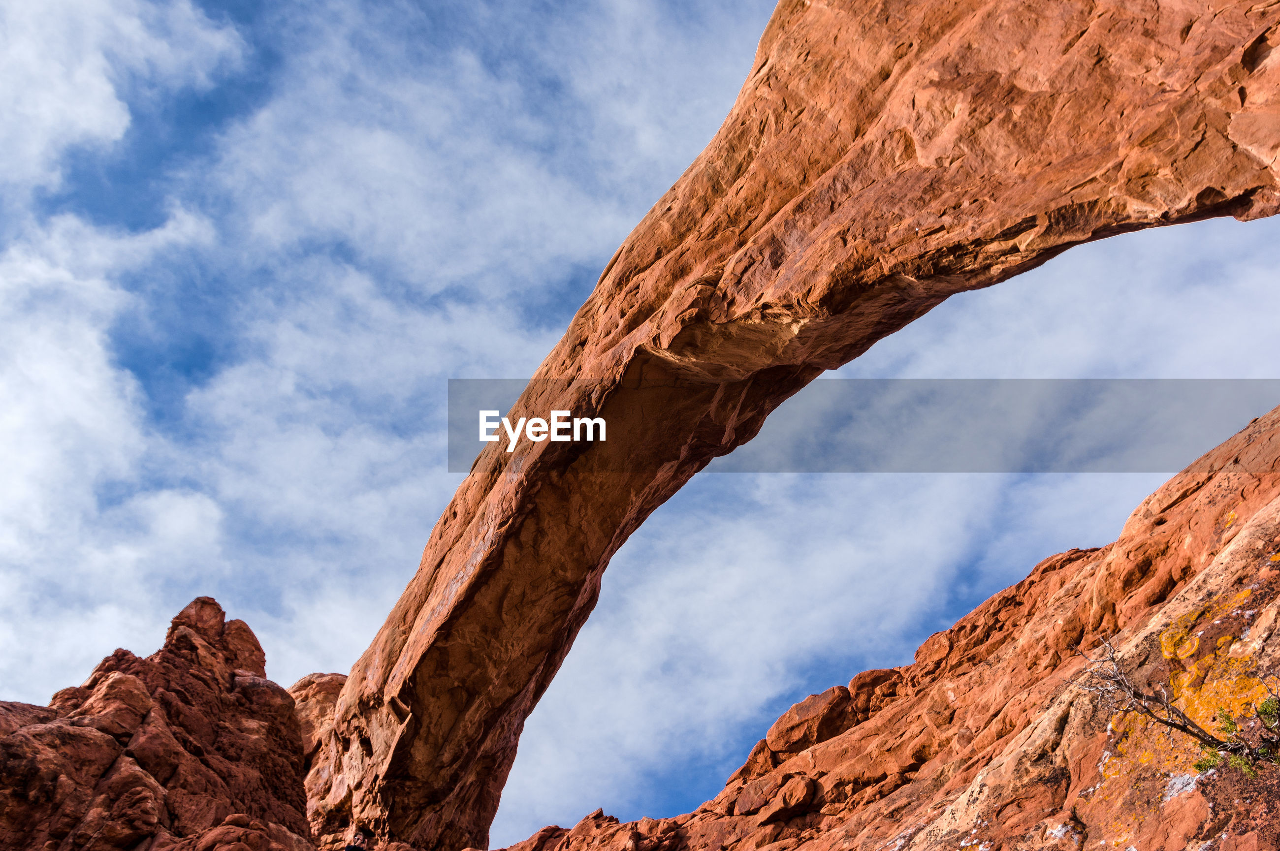 Low angle view of rock formations at arches national park against cloudy sky