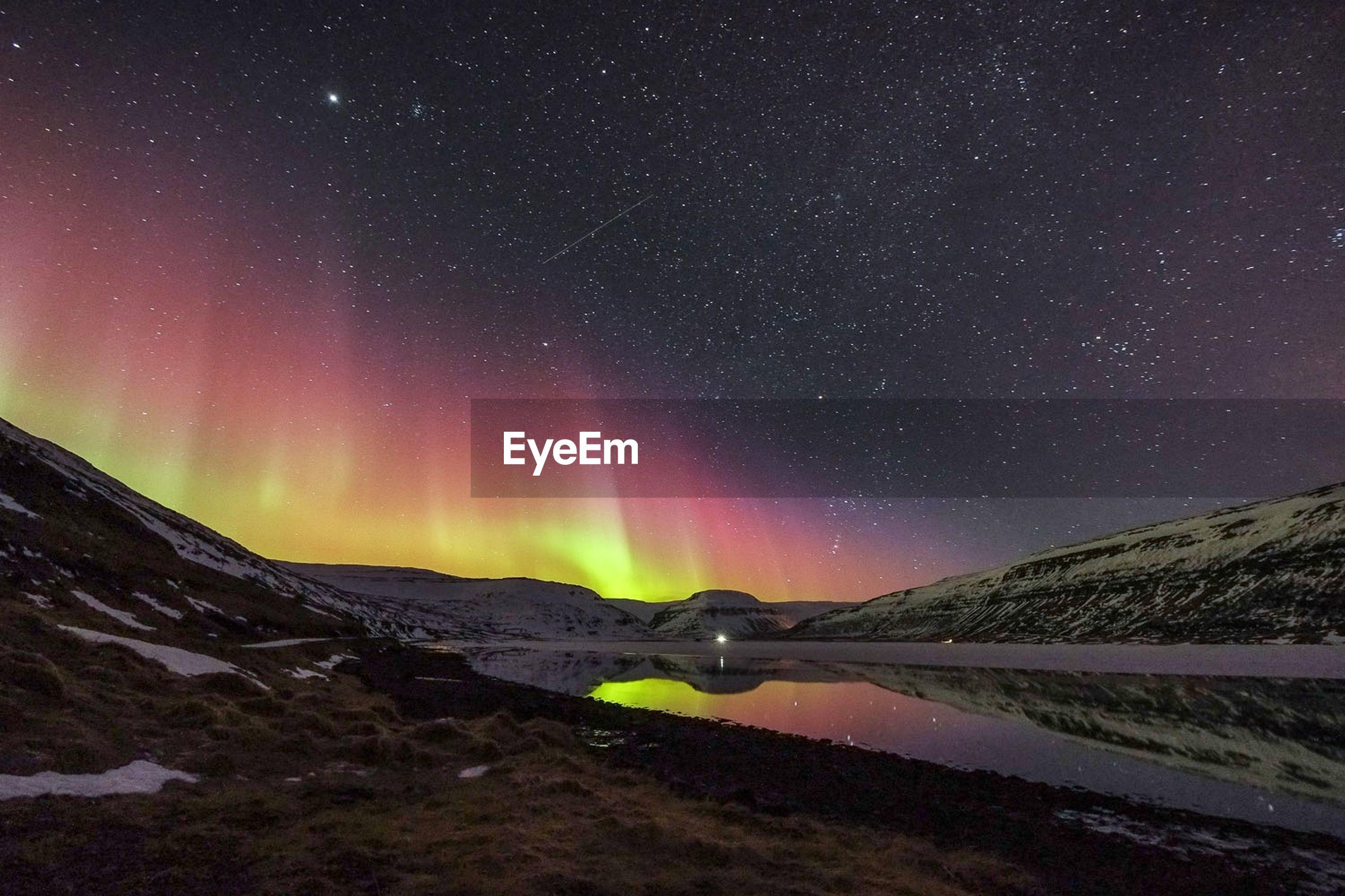 Aurora borealis on lake and landscape at night