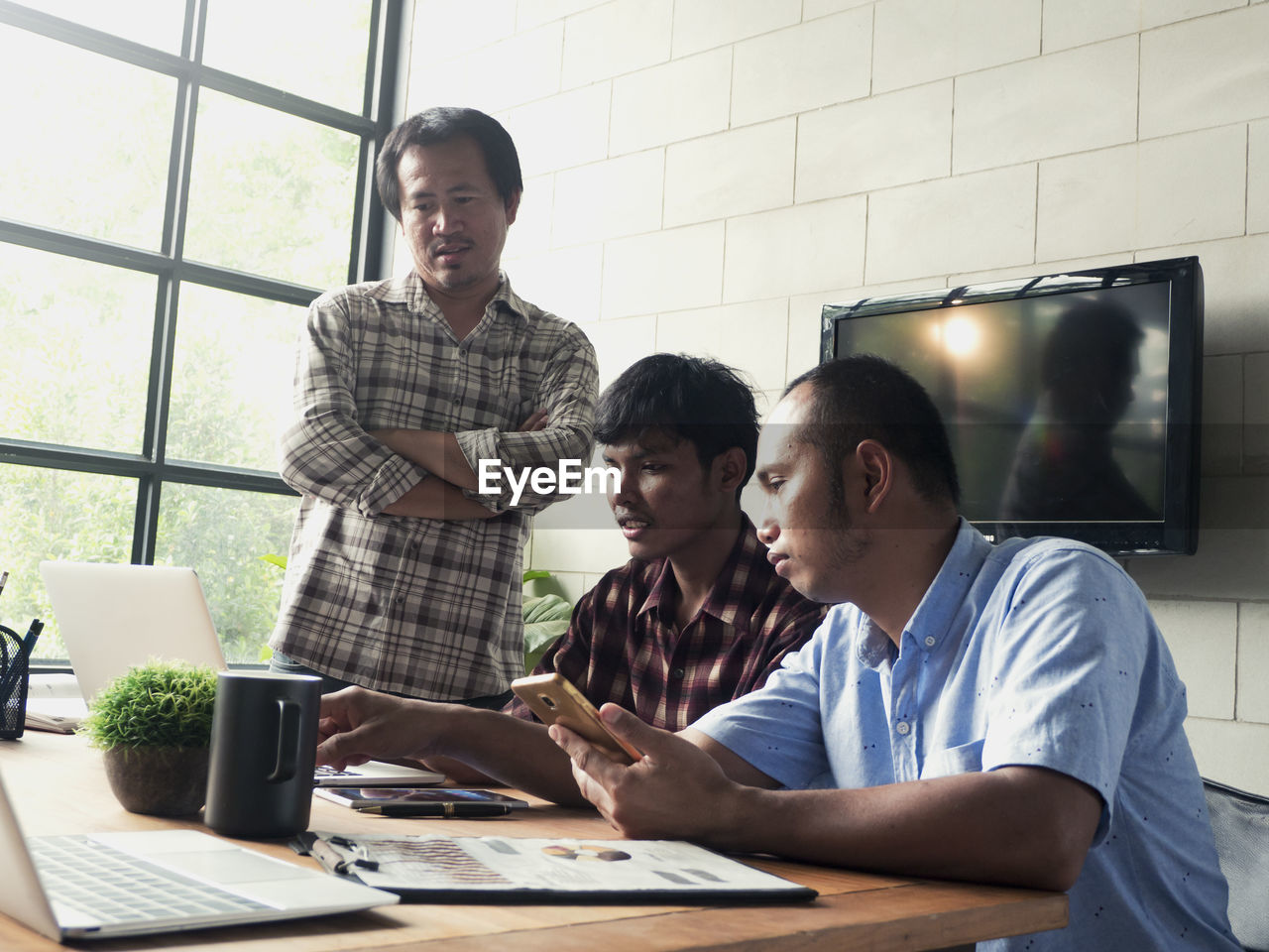 young men, table, real people, wireless technology, technology, males, men, waist up, casual clothing, indoors, computer, young adult, connection, people, communication, laptop, group of people, cooperation, adult, sitting, using laptop, coworker