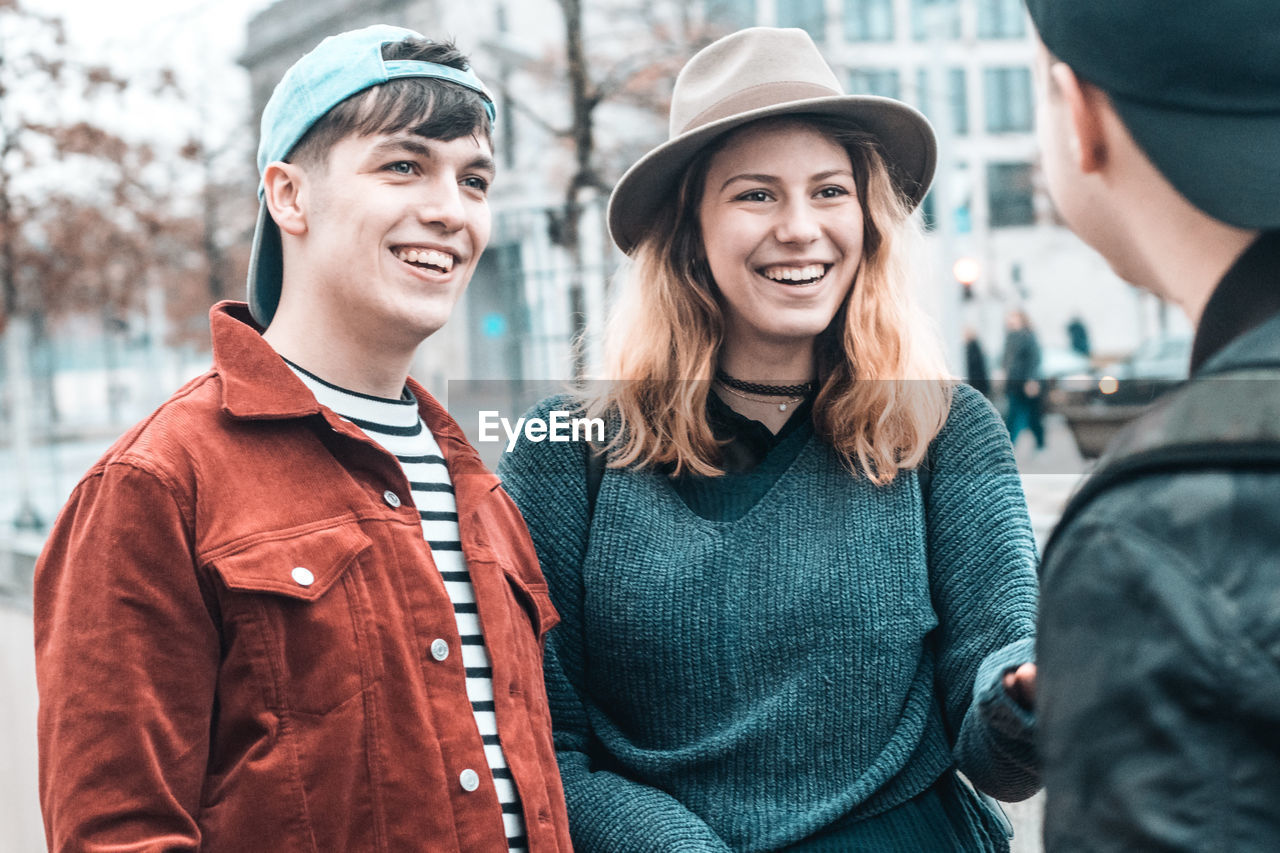 smiling, young adult, portrait, young women, two people, togetherness, young men, clothing, emotion, happiness, real people, lifestyles, leisure activity, focus on foreground, looking at camera, friendship, casual clothing, men, women, couple - relationship, outdoors, hairstyle