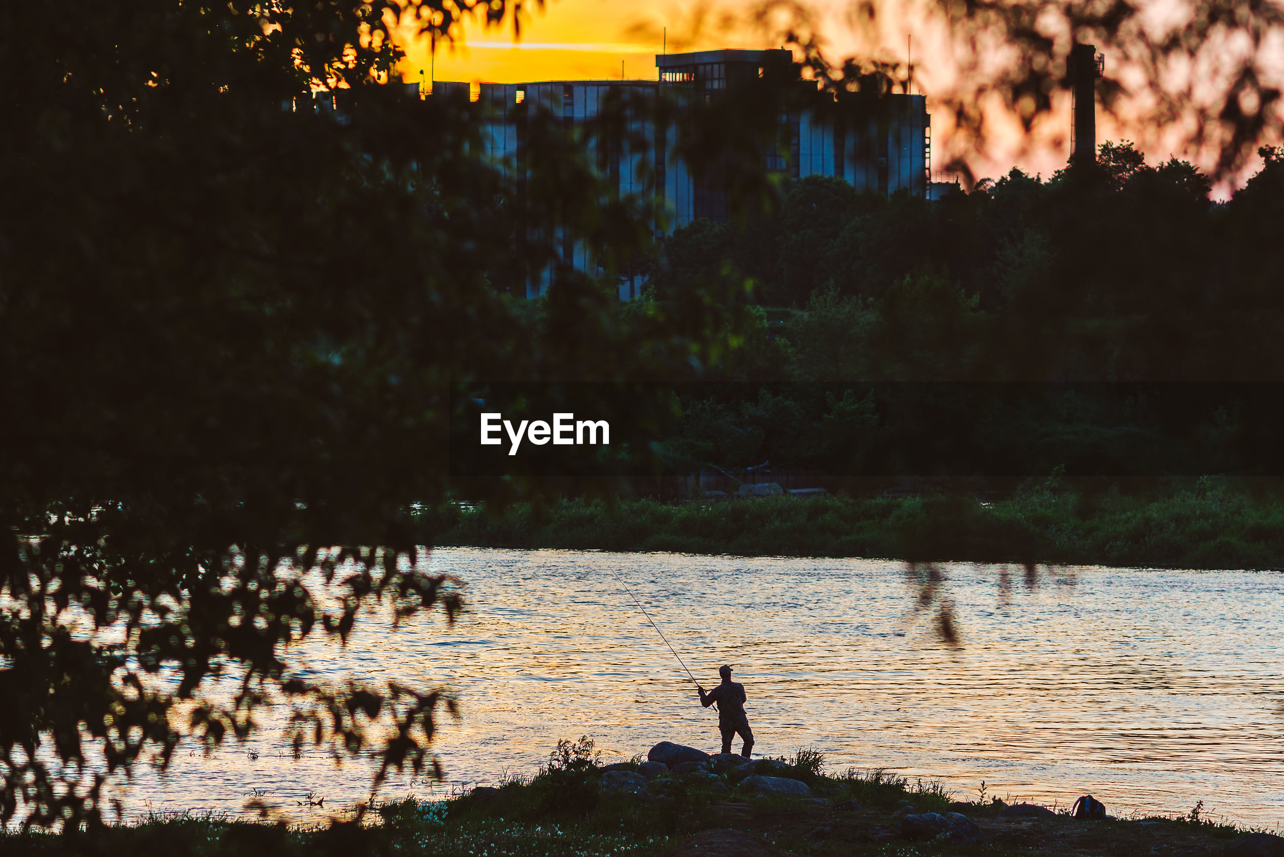 Silhouette man fishing by river during sunset