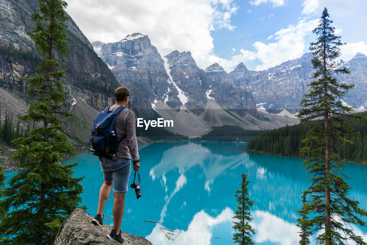 Rear View Of Man Standing On Rock While Looking At Mountains Against Sky