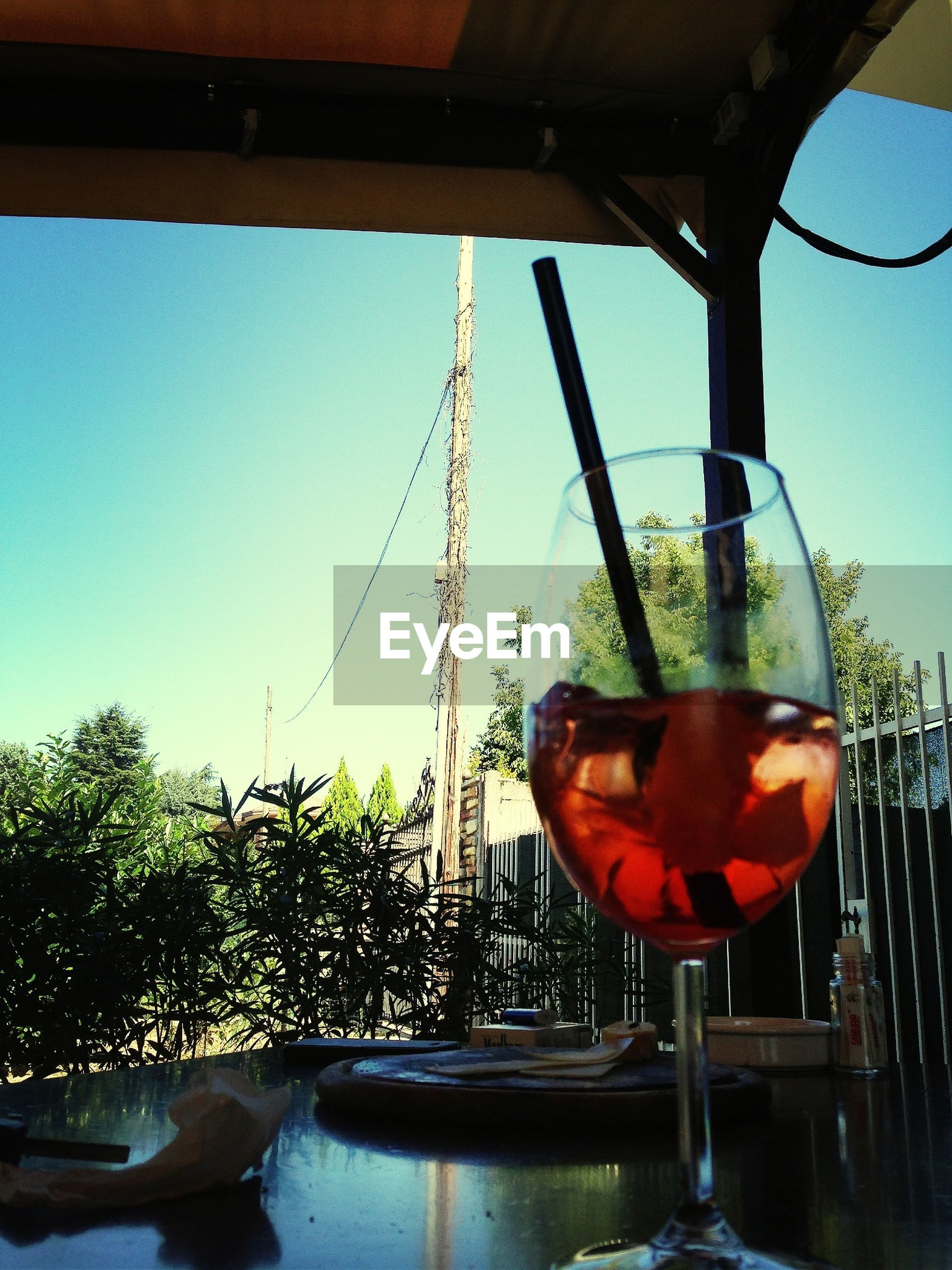 clear sky, food and drink, table, indoors, glass - material, sunlight, window, close-up, no people, transparent, built structure, tree, day, hanging, chair, house, architecture, metal, sky
