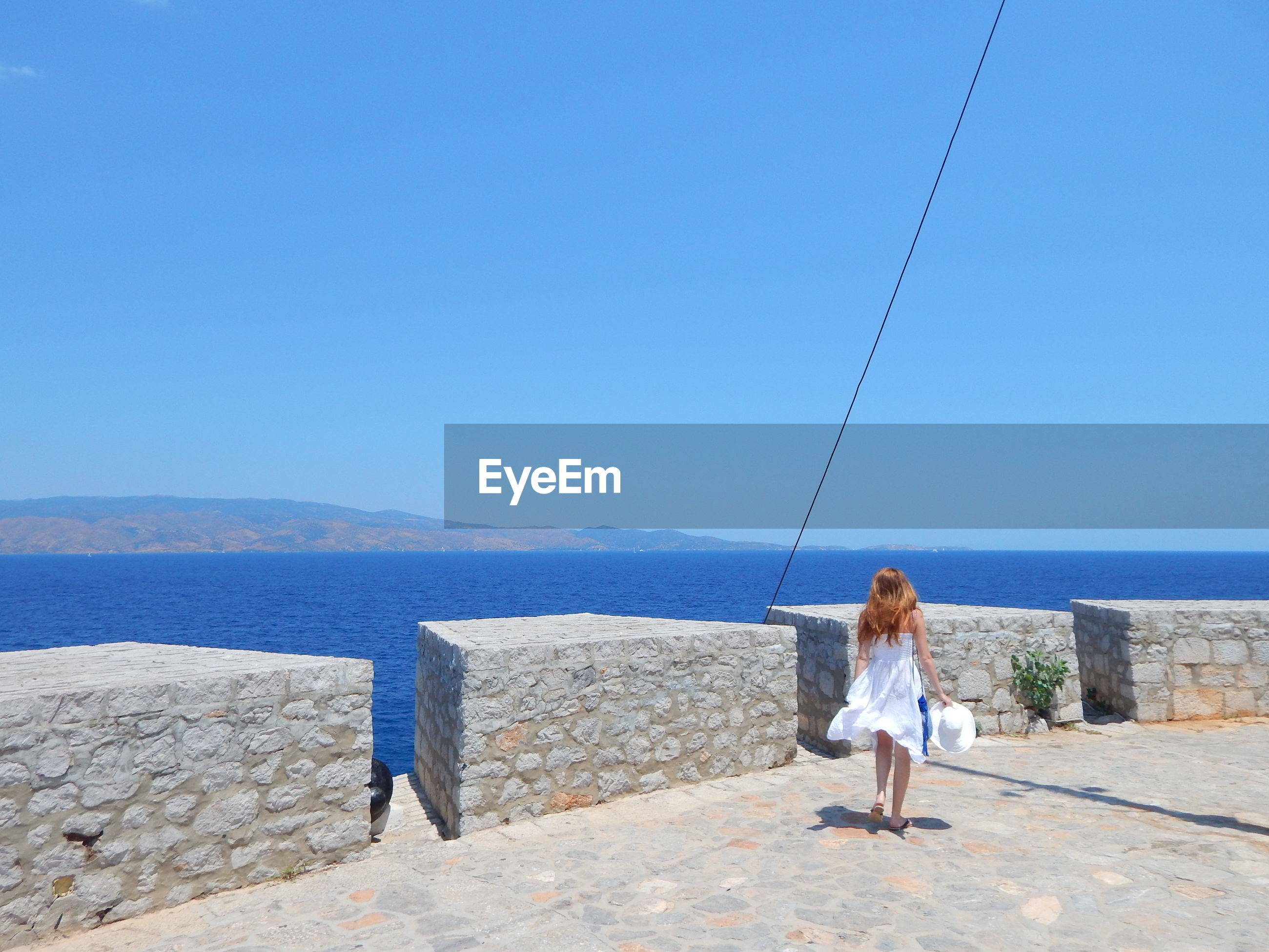 Full length of woman in white dress walking at observation point by sea against clear sky
