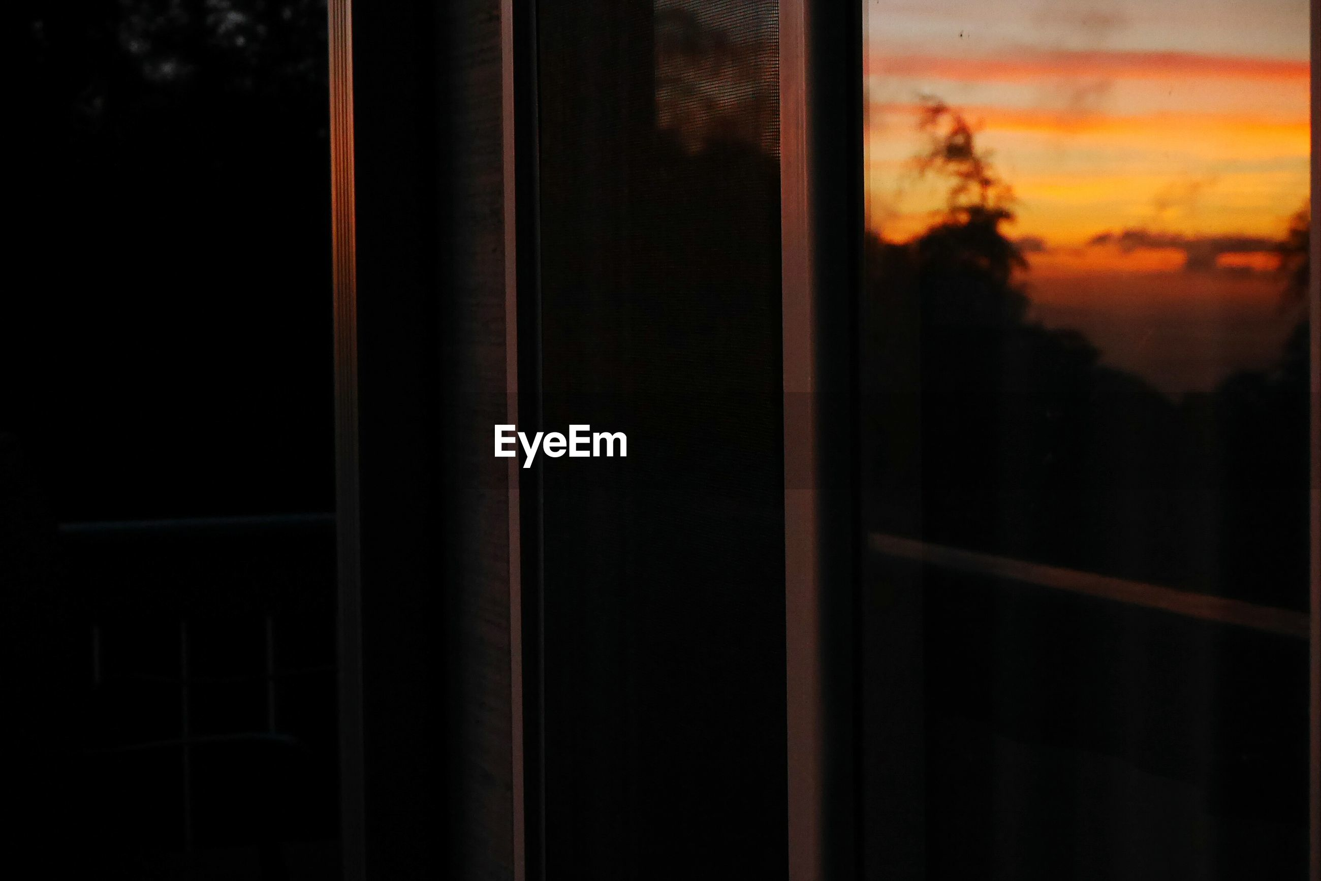Close-up of window in building during sunset