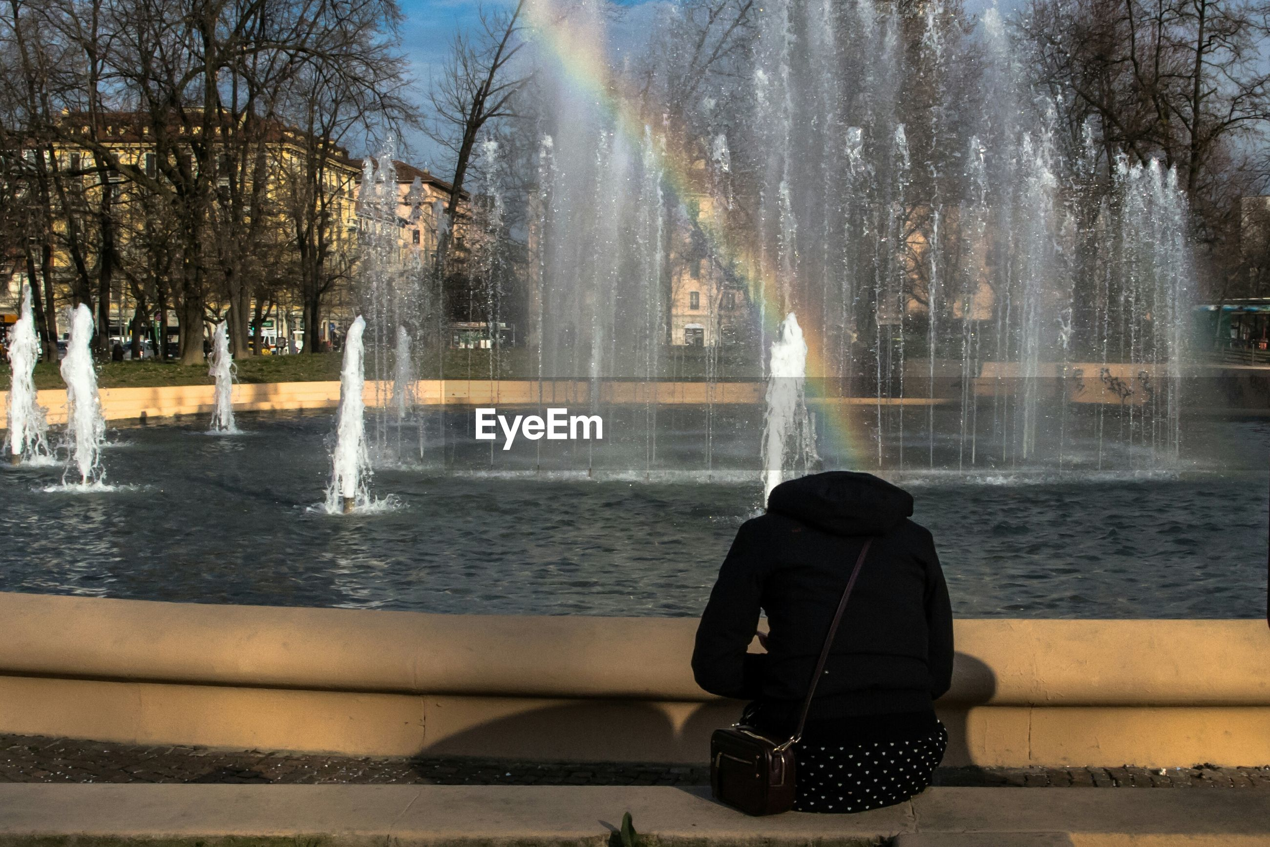 Rear view of woman sitting by fountain in park