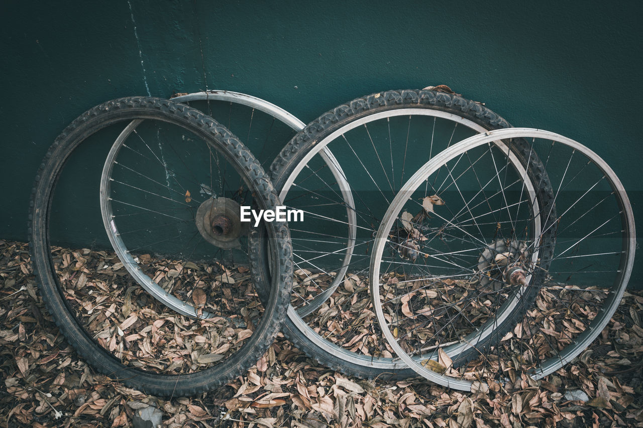 transportation, wheel, metal, mode of transportation, land vehicle, no people, day, abandoned, outdoors, bicycle, obsolete, wall - building feature, old, stationary, high angle view, damaged, nature, architecture, close-up, land, spoke, tire, wagon wheel
