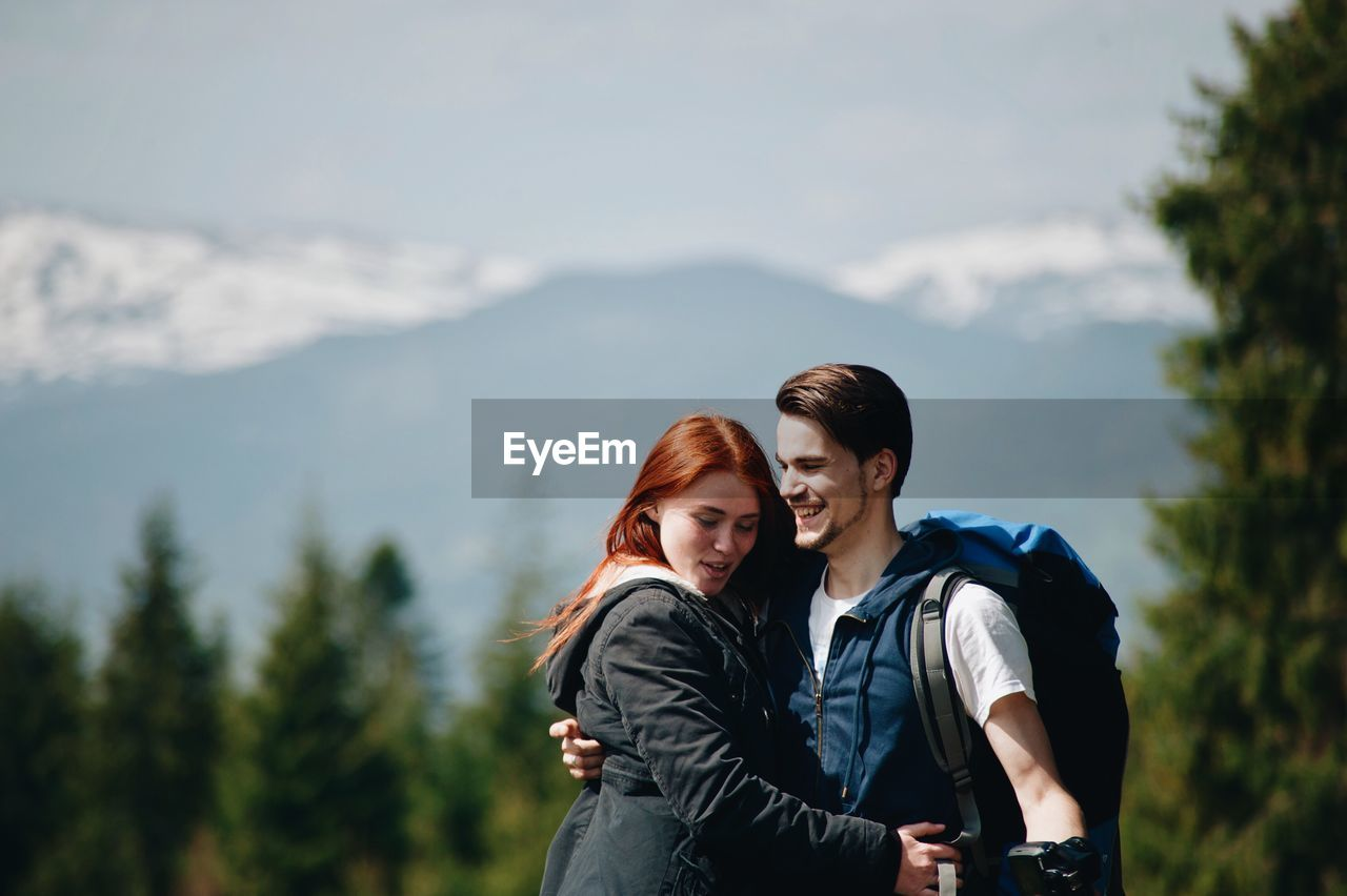 Cheerful couple embracing against mountain