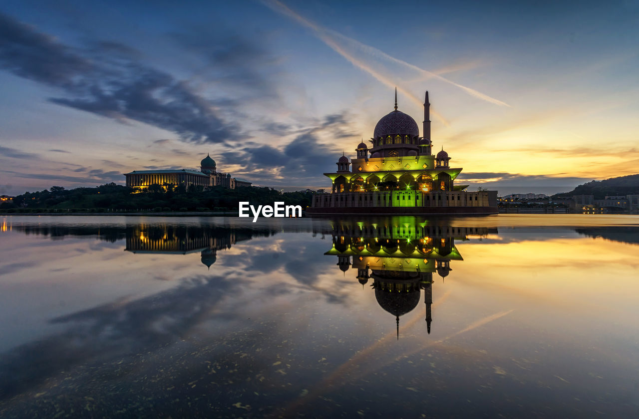 water, building exterior, sky, reflection, built structure, architecture, cloud - sky, waterfront, belief, religion, lake, building, spirituality, sunset, nature, place of worship, symmetry, illuminated, no people, outdoors, government