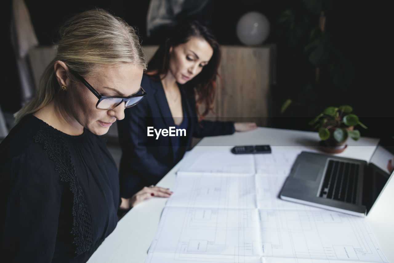office, business, adult, working, women, business person, table, businesswoman, young adult, communication, glasses, indoors, computer, two people, young women, real people, wireless technology, technology, planning, eyeglasses, blueprint, design professional, teamwork, new business, using laptop, architect