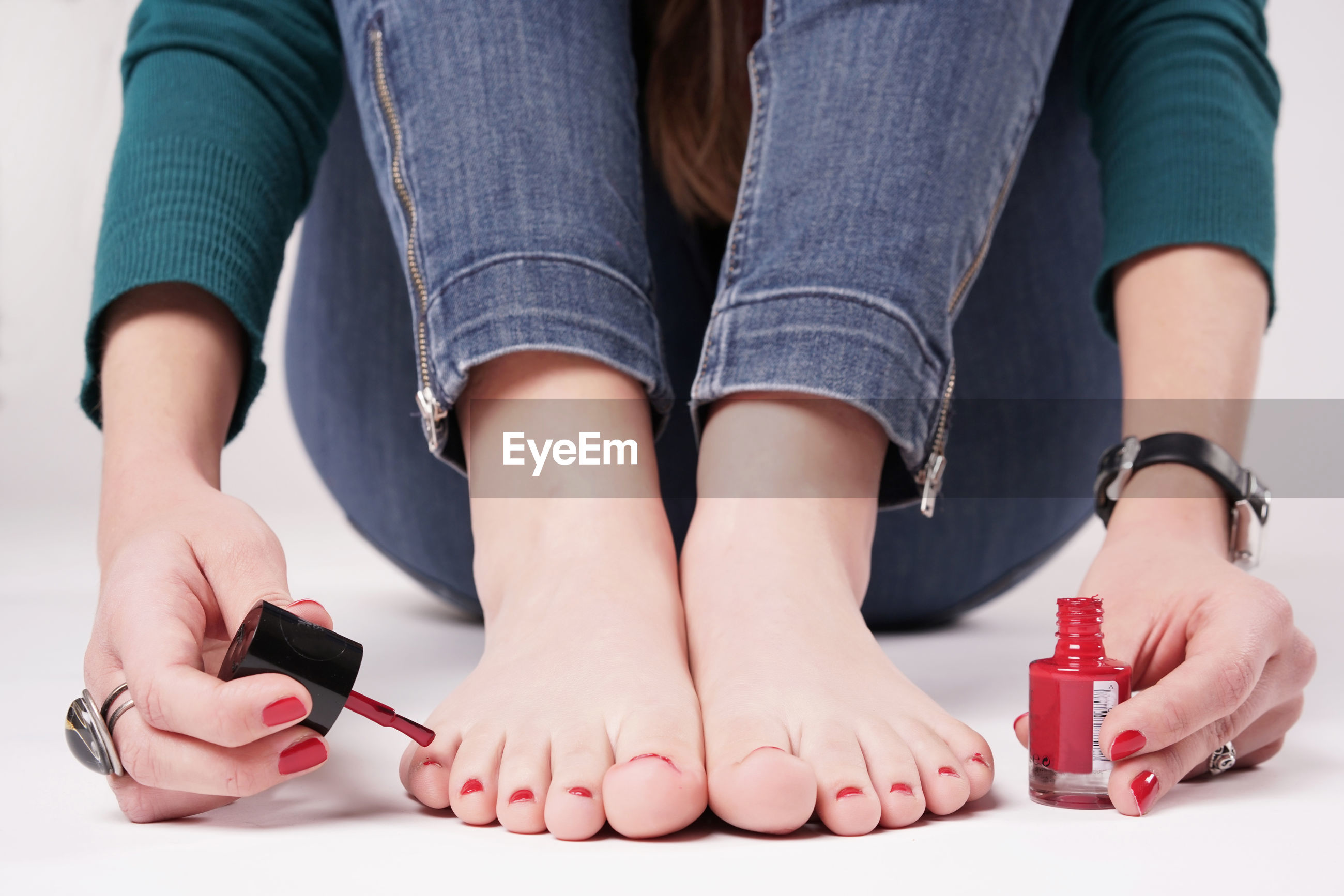 Woman painting her toe nails against white background