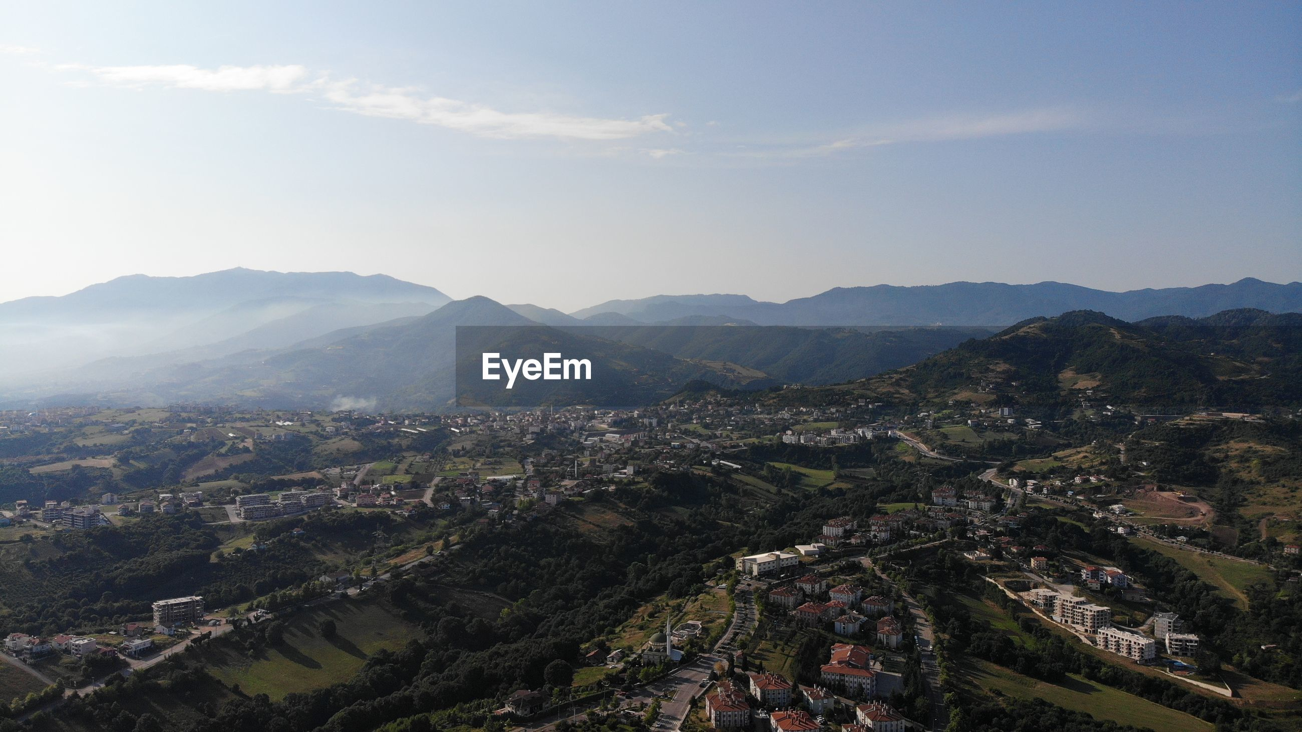 HIGH ANGLE VIEW OF TOWNSCAPE BY MOUNTAINS AGAINST SKY