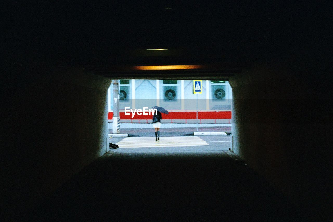 transportation, indoors, real people, mode of transportation, full length, architecture, public transportation, day, people, dark, illuminated, built structure, tunnel, men, motor vehicle, silhouette, lifestyles, car, parking garage, light at the end of the tunnel