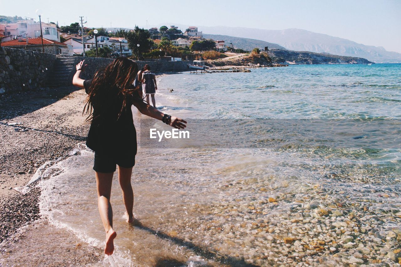 Girl jumping on shore at beach