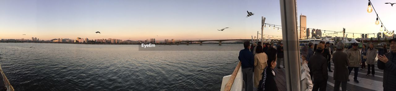 sky, sunset, real people, large group of people, group of people, crowd, architecture, panoramic, men, city, built structure, building exterior, nature, water, adult, leisure activity, women, street, outdoors