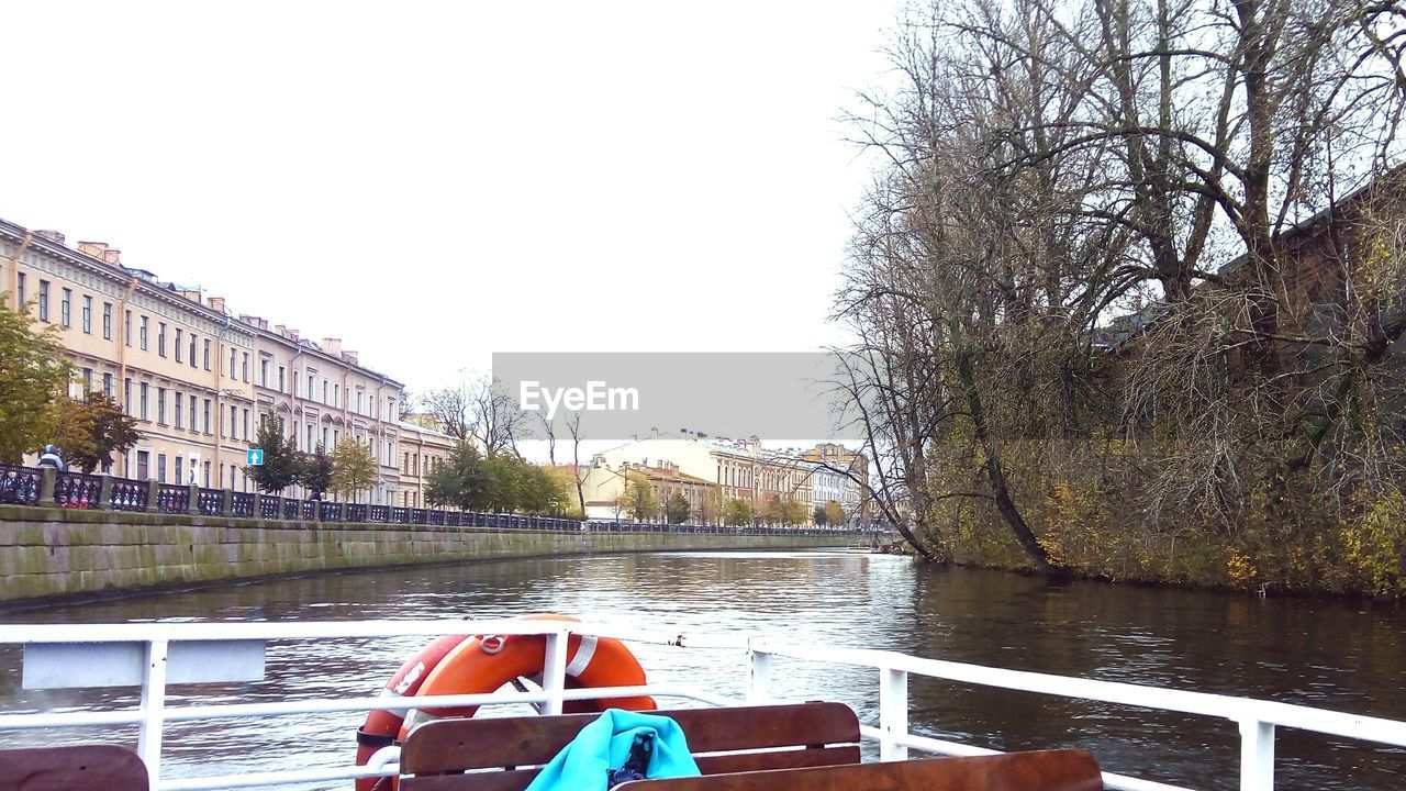 river, water, tree, built structure, architecture, transportation, day, building exterior, outdoors, clear sky, bare tree, nautical vessel, no people, mode of transport, nature, sky