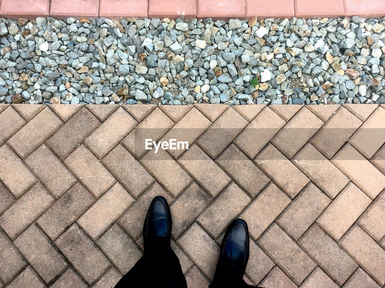high angle view, low section, shoe, body part, stone - object, human leg, human body part, day, solid, stone, standing, personal perspective, large group of objects, one person, footpath, real people, abundance, pattern, nature, outdoors, pebble, human foot, paving stone, gravel, human limb