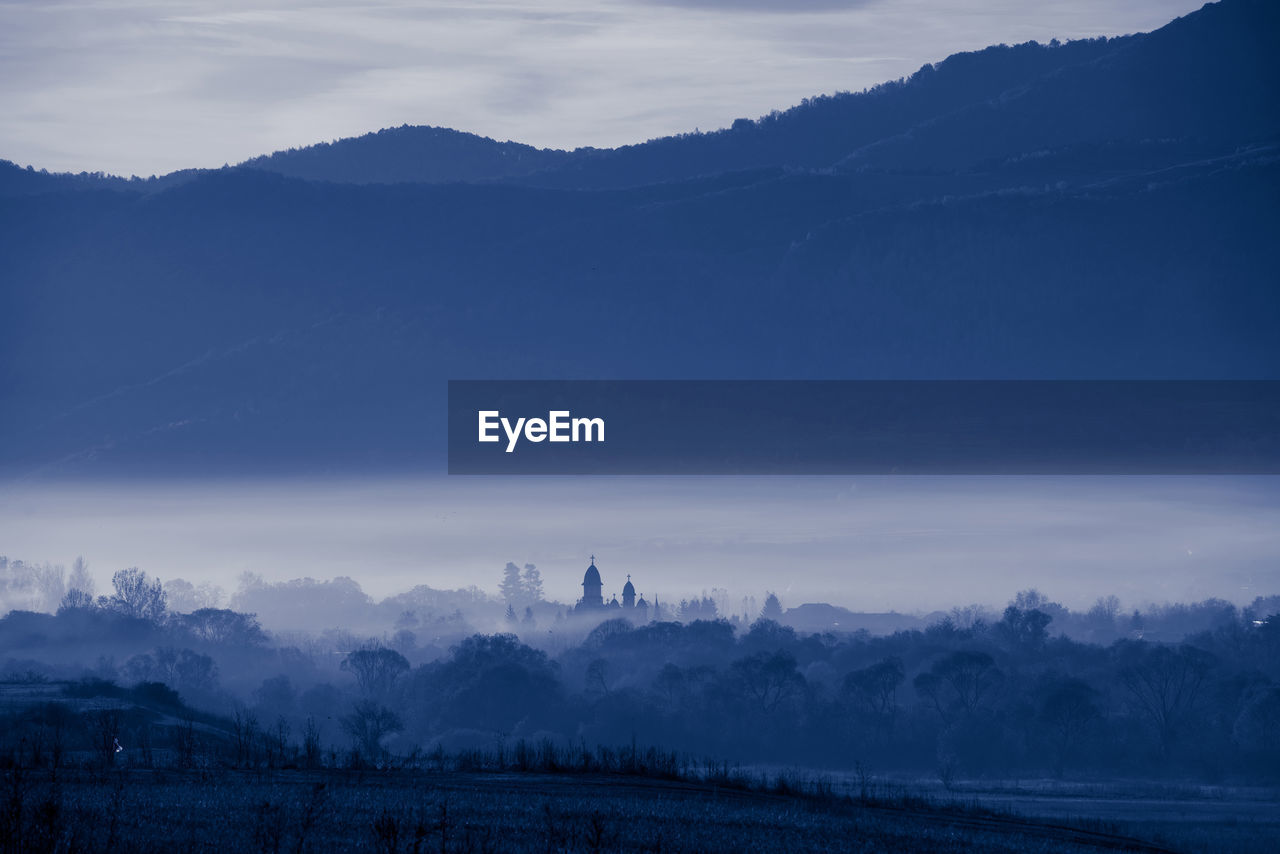 Scenic View Of Silhouette Mountains During Foggy Weather