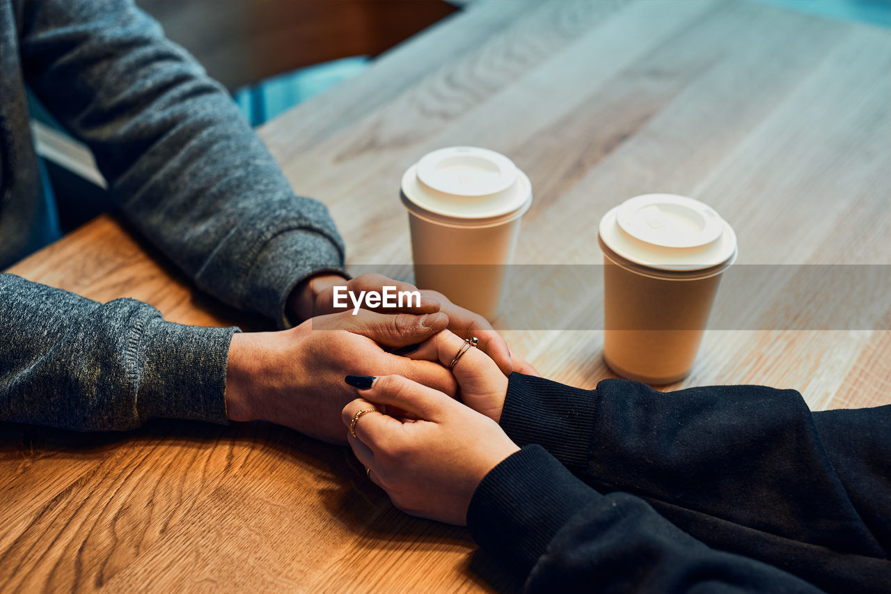 Loving couple holding hands sitting in cafe drinking coffee. loving people. valentines day