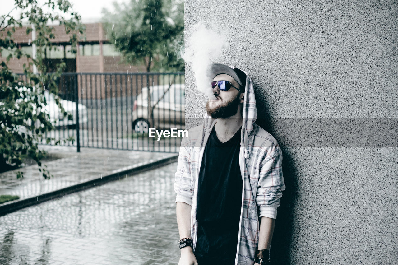 Close-Up Of Young Man Smoking While Standing By Wall During Rain