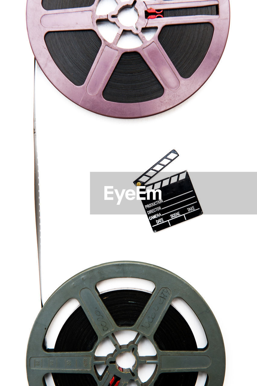 Directly above shot of film reels and movie slate on white background