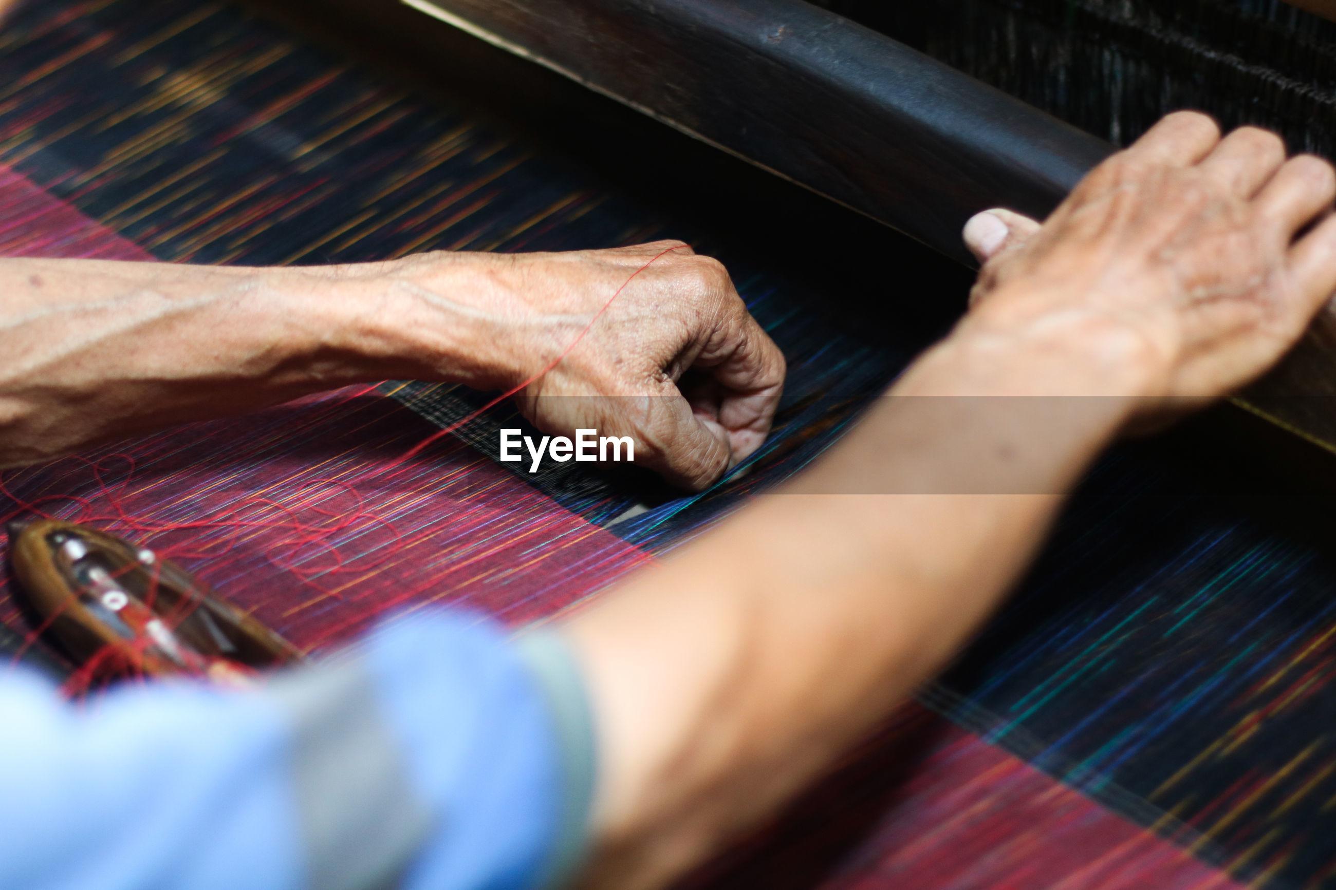 Cropped hands weaving loom